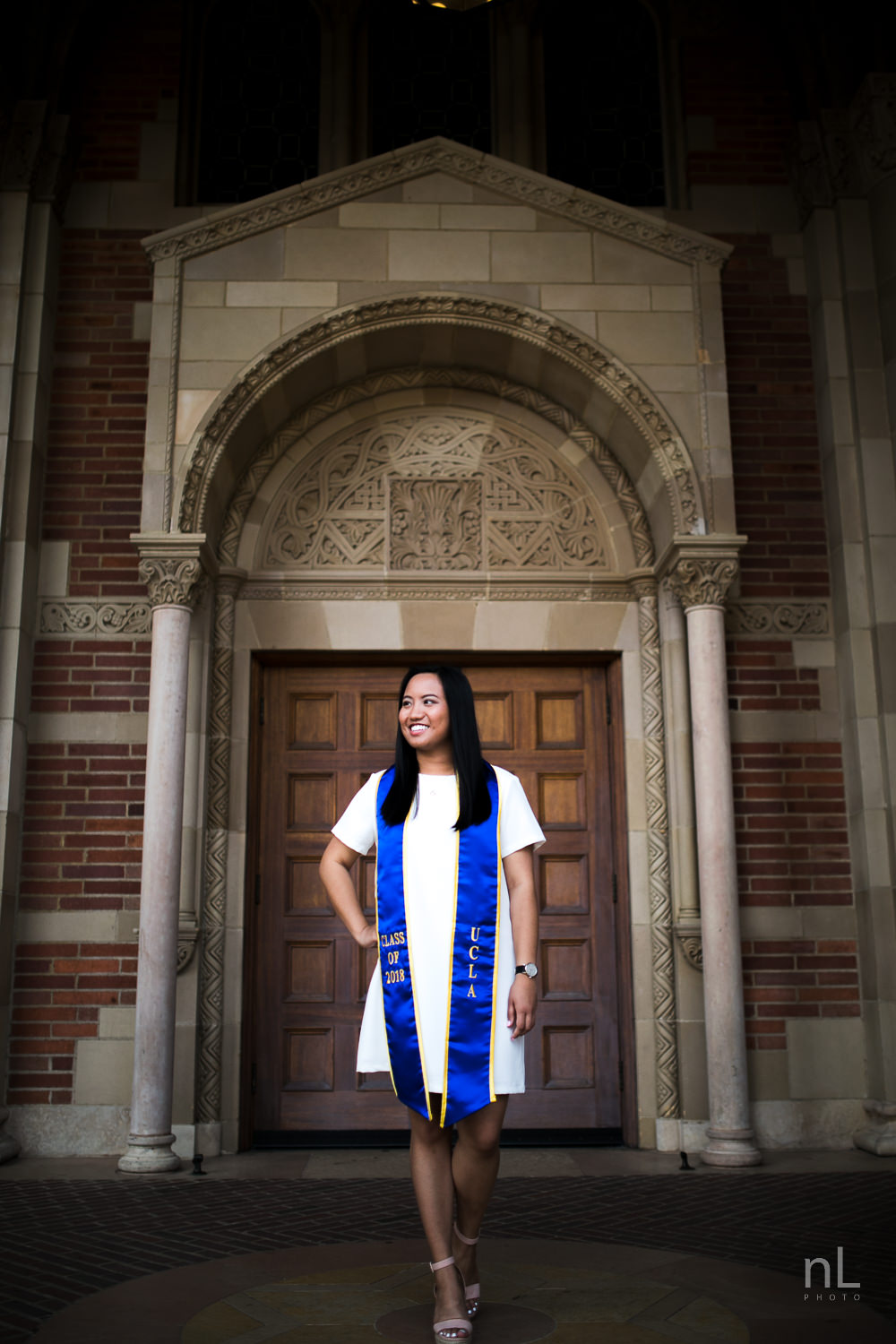 A portrait of a girl in front of the Royce Hall front doors.