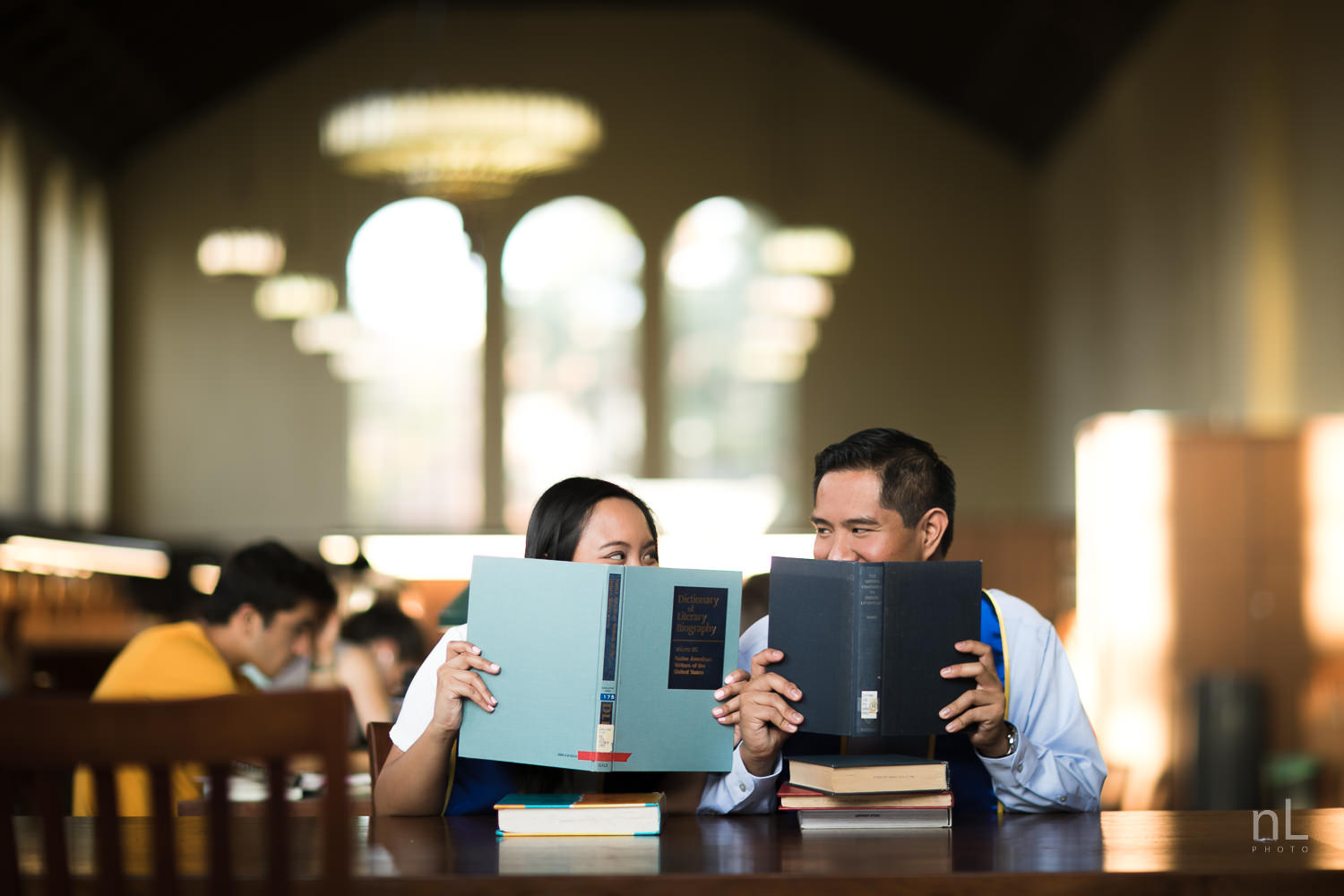 A portrait of brother and sister in the Powell Library Reading Room smiling behind books.