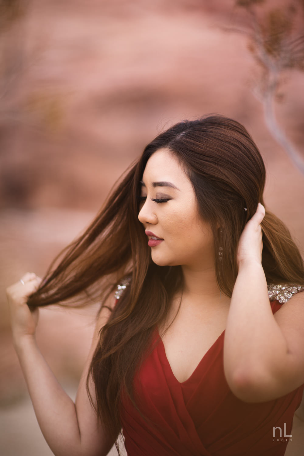 Portrait of Asian model in long, flowing, red dress, running hand through hair in Red Rock Canyon.