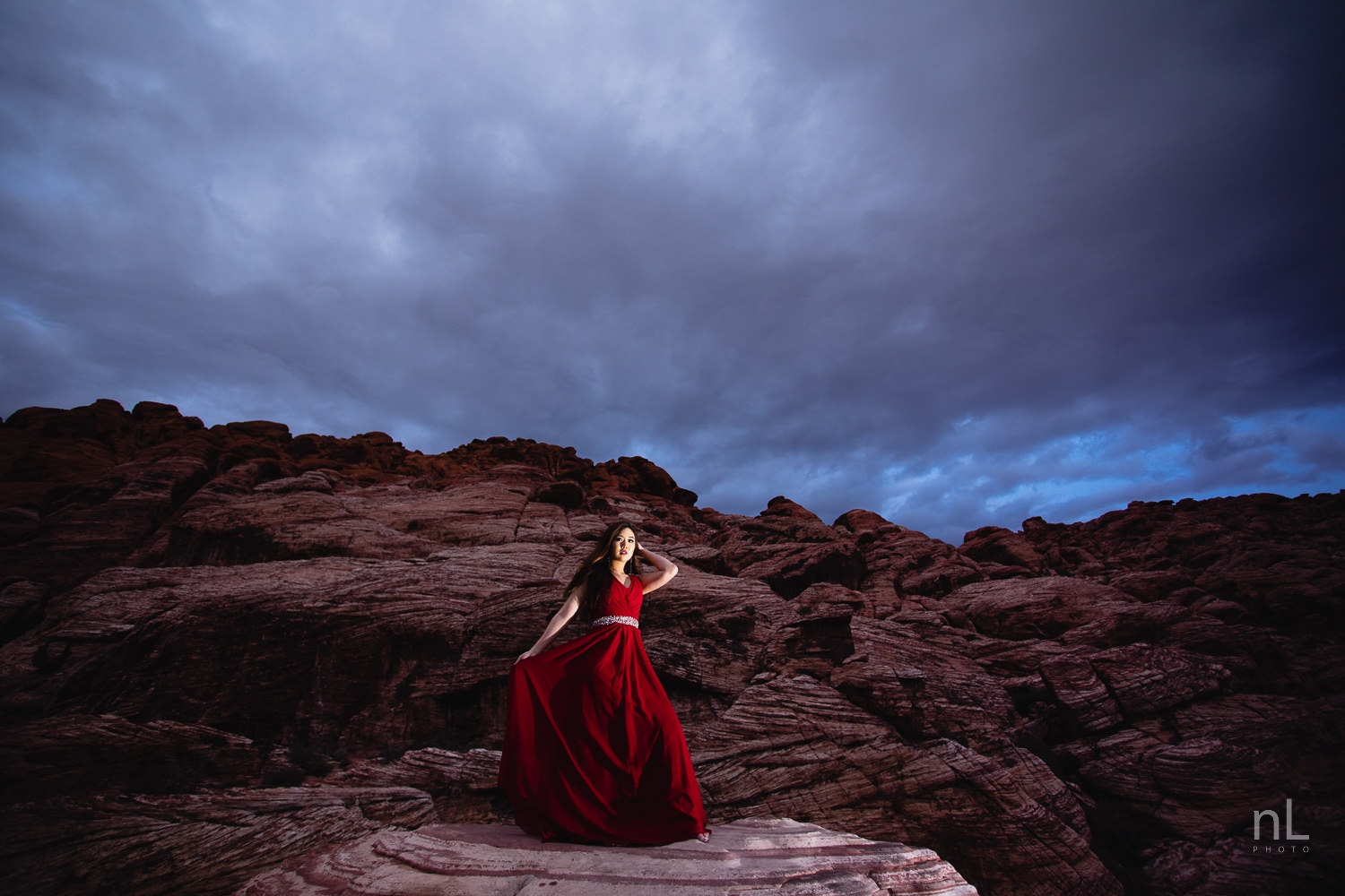 Epic environmental portrait of Asian model in long, flowing, red dress, standing on in Red Rock Canyon during dusk and stormy clouds in background.