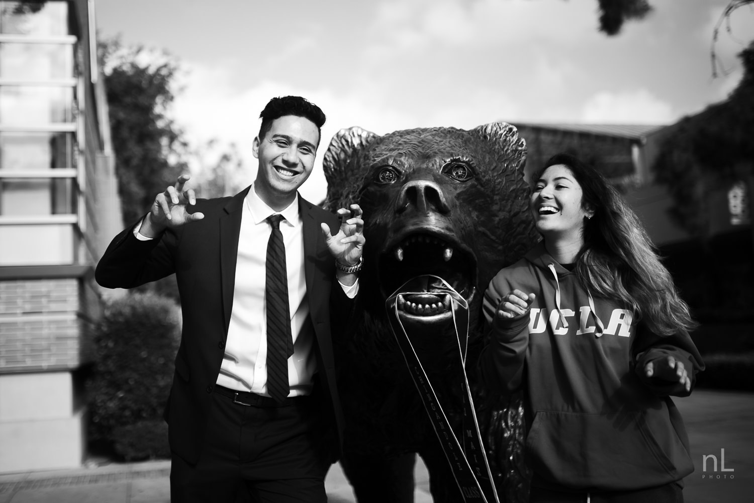 UCLA Class of 2019 graduate wearing suit and tie and graduation sash with girlfriend posing in front of Bruin Bear.