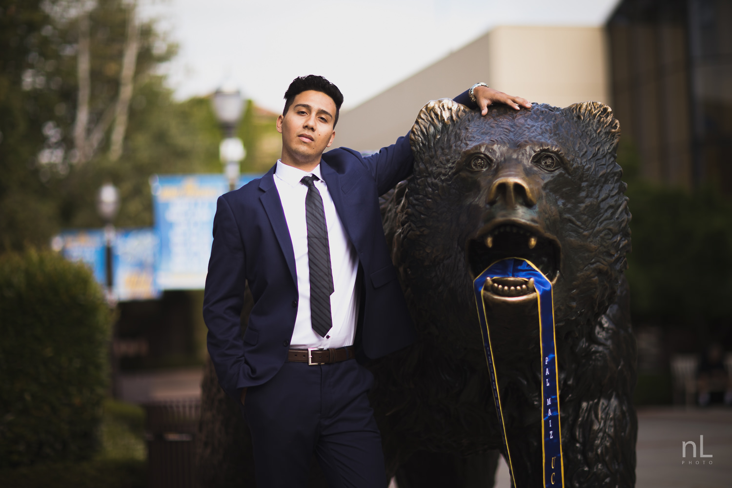 UCLA Class of 2019 graduate wearing suit and graduation sash at Bruin Bear.