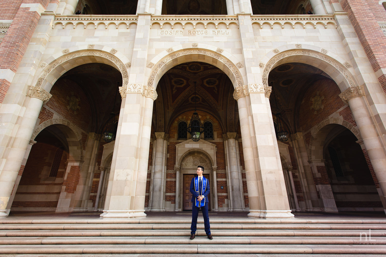 UCLA Class of 2019 graduate wearing suit and tie and graduation sash standing in front of Royce Hall.