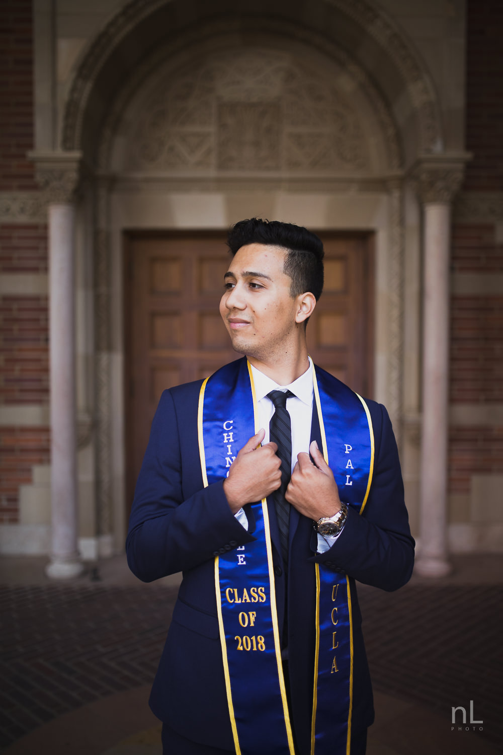 UCLA Class of 2019 graduate wearing suit and tie and graduation sash smiling and standing in front of Royce Hall.