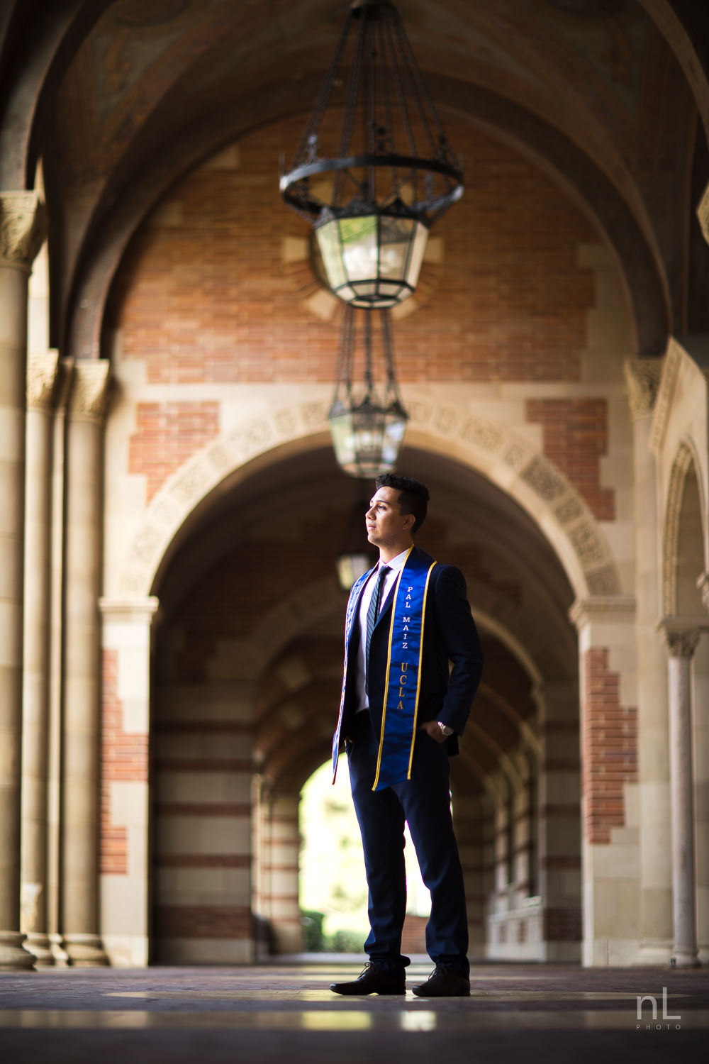 UCLA Class of 2019 graduate wearing suit and tie and graduation sash smiling and standing in Royce Hall arches.