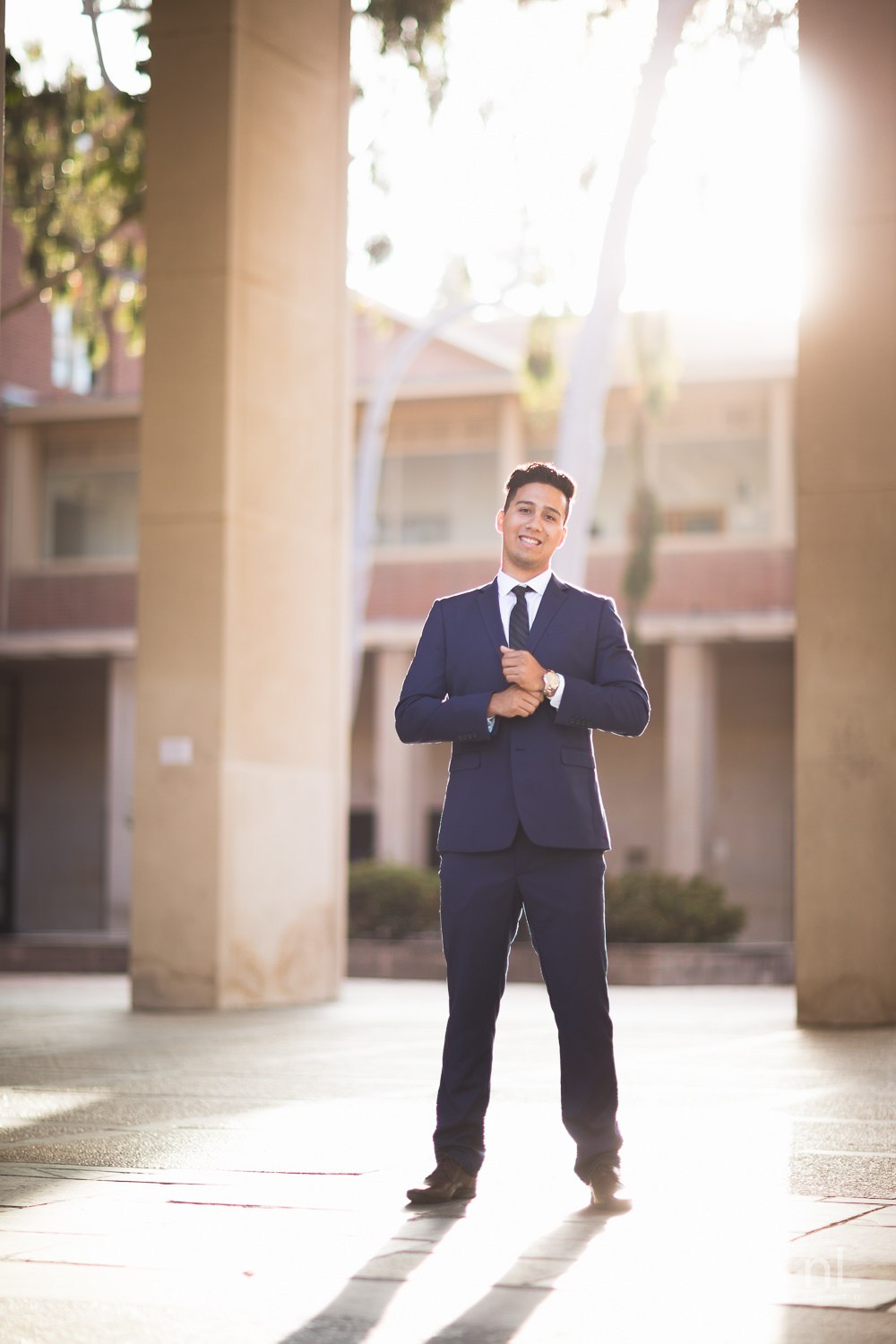 UCLA Class of 2019 graduate wearing suit and tie and graduation sash looking serious in front of Young Hall.