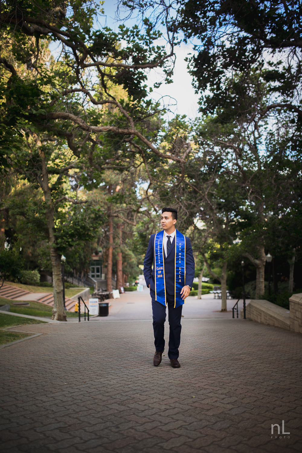 UCLA Class of 2019 graduate wearing suit and tie and graduation sash walking down Bruinwalk.