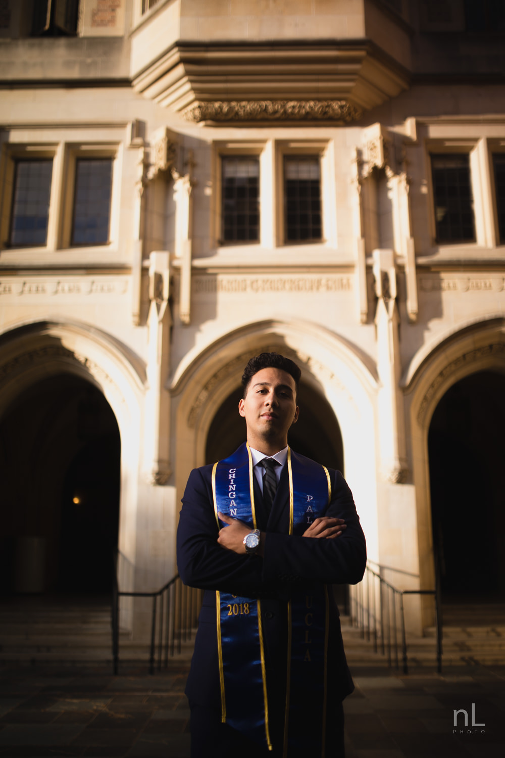 UCLA Class of 2019 graduate wearing suit and tie and graduation sash looking serious in front of Kerckhoff Hall.