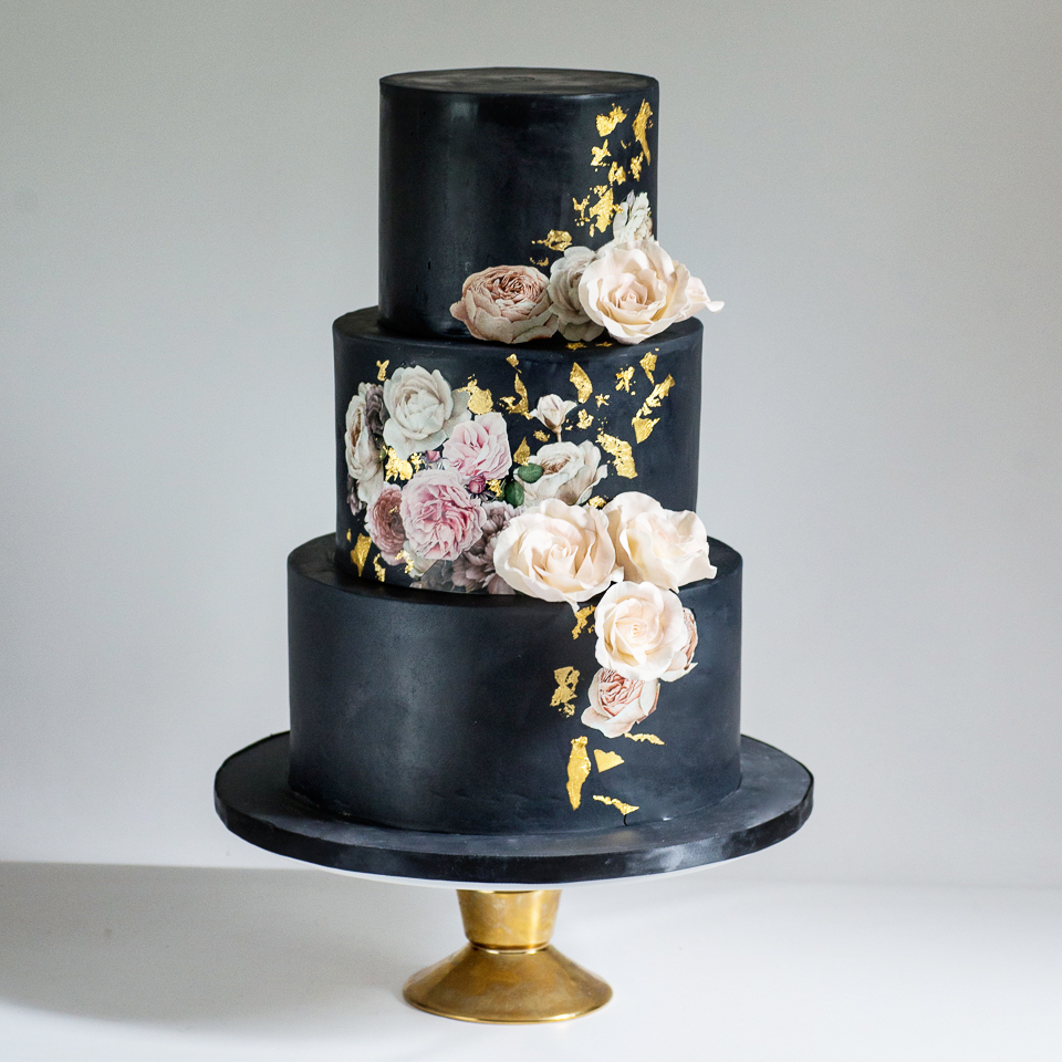 Black wedding cake with sugar roses, floral images, and gold leaf