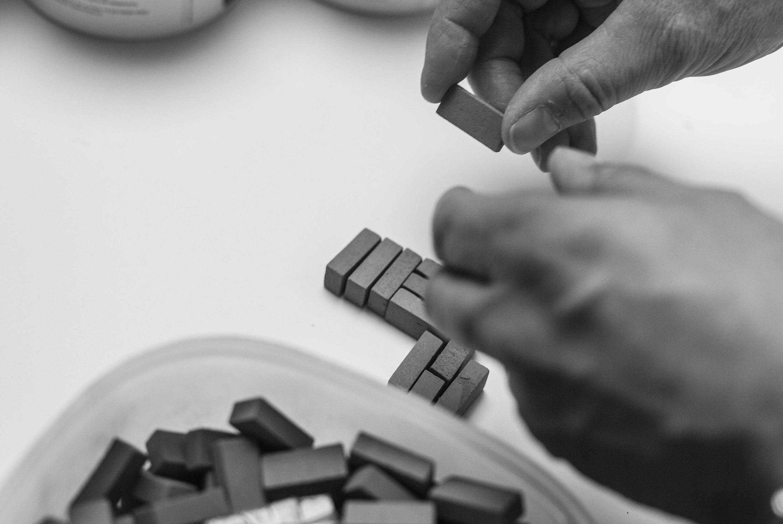 Hantverk.  Ett tegelmönster i miniatyr växer fram i arkitektkontorets verkstad.