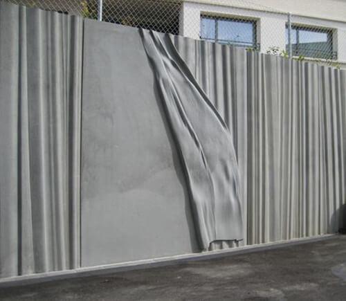 Draperat.  Sockelvåningen av formgjuten betong eller profilerad puts utformas som ett draperi som dras isär där fönster, dörrpartier och lokaler tittar fram.