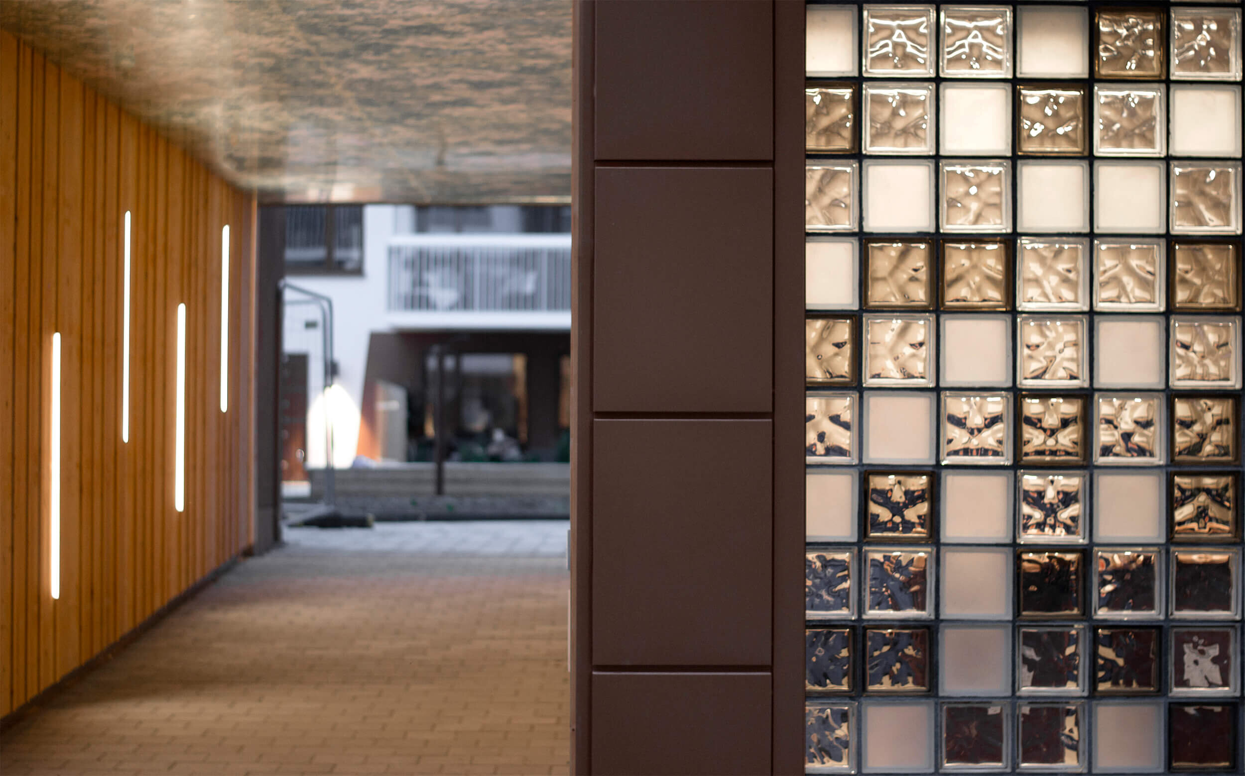 Glasbetong i miljörummet skapar värme - Varje miljörum hör ihop med en plats. Ljusinsläppen ger på dagen en trevligare, varmare inomhusmiljö. På kvällen bidrar belysningen till en intressant prisma som lyser upp gatan. Inslag av rödbruna glas knyter an till husets färgskala