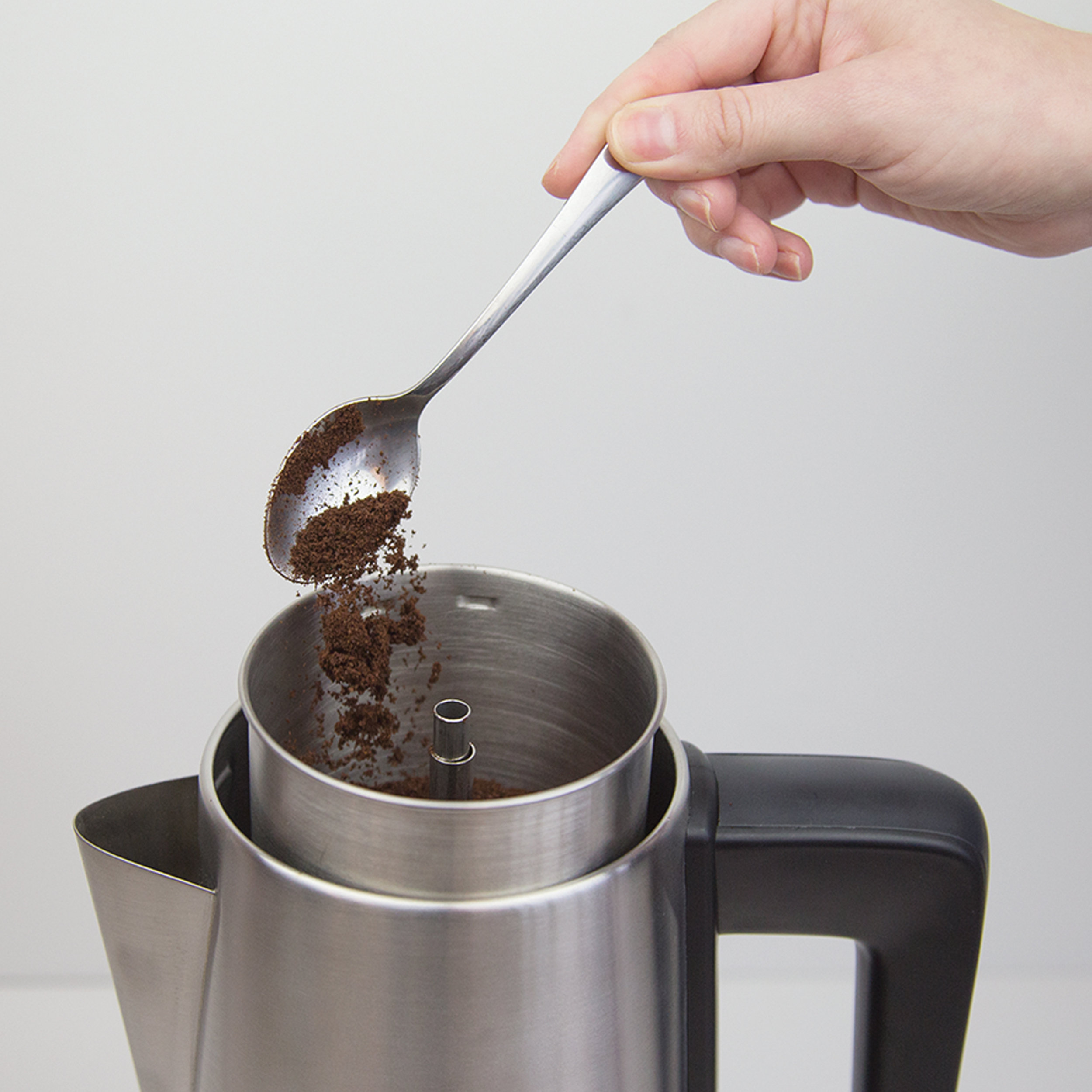 Putting a spoon of grind coffee in the 1.5L Electric Coffee Percolator