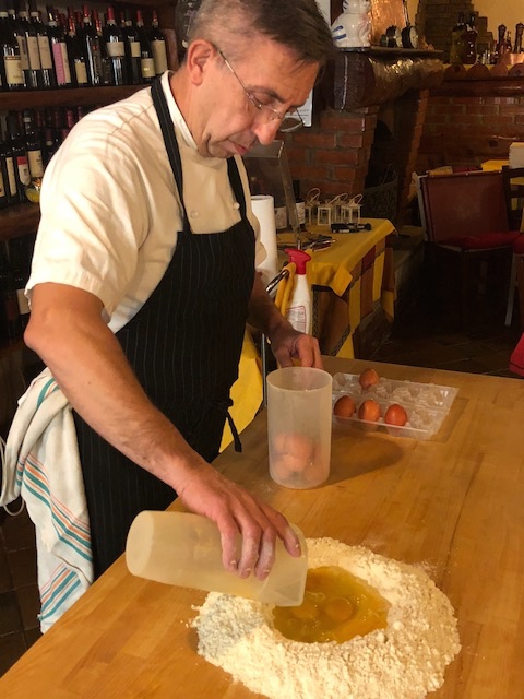 carefully pouring eggs into the flour well for pasta