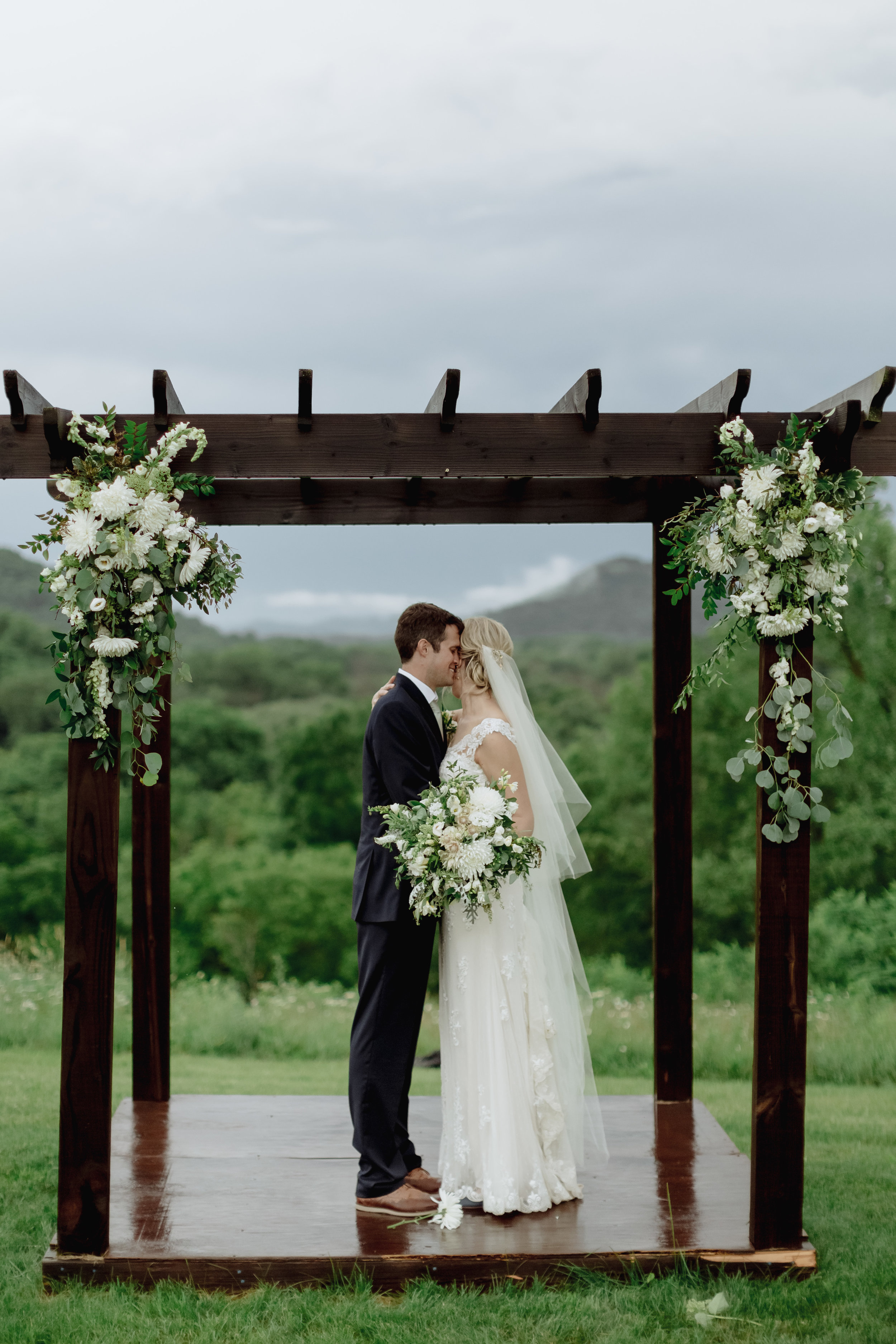 Thankfully the storms subsided post-ceremony long enough for them to get some beautiful hilltop photos (those poor arch flowers took a beating in the rain!).