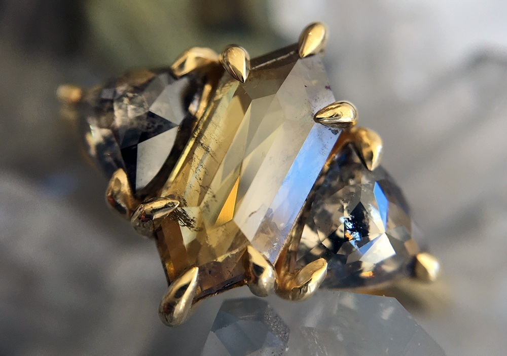 The Golden Hexagon - A golden-hued lesson in sacred geometry, with an elongated hexagon cut yellow diamond flanked by two perfectly paired salt + pepper trillions.