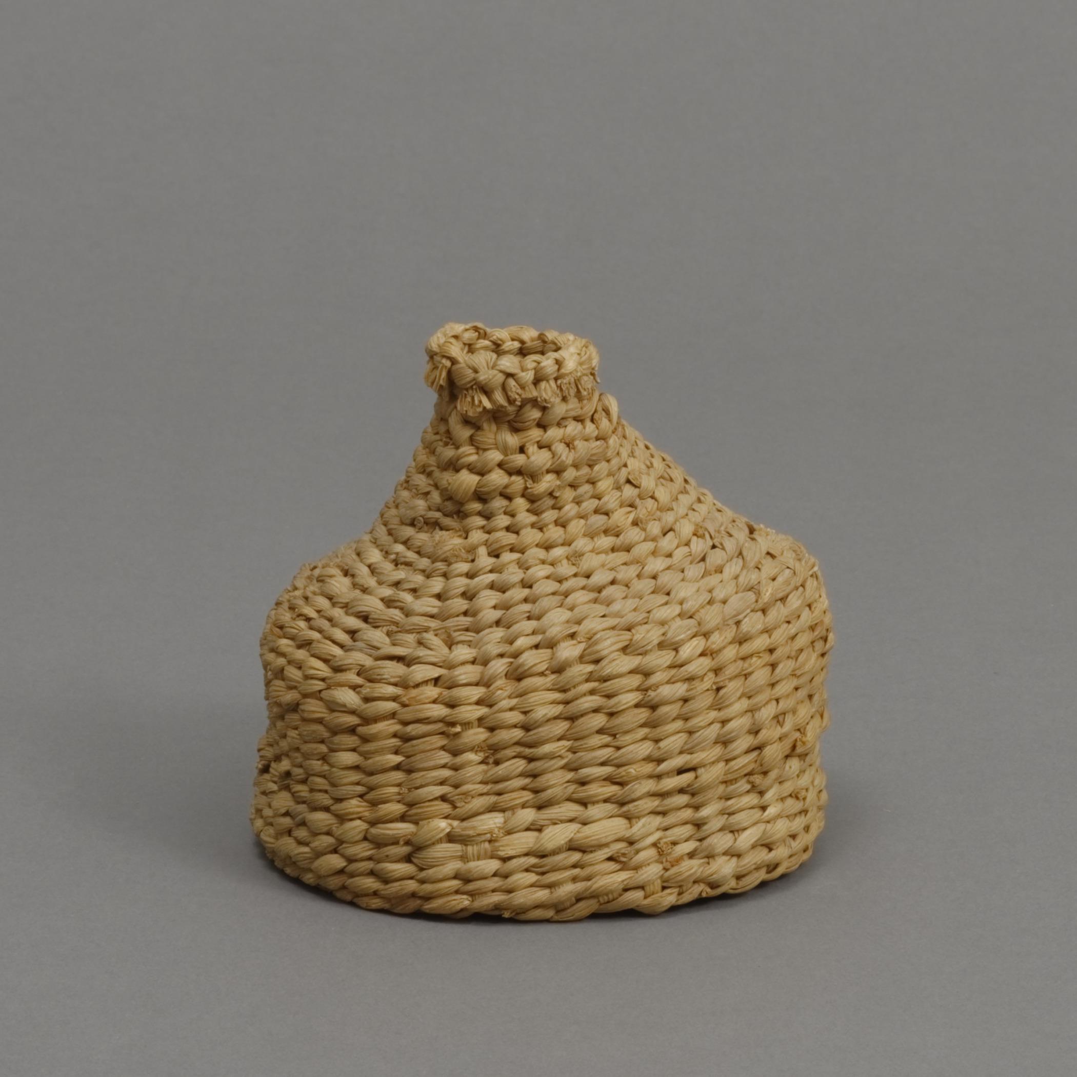 Haudenosaunee (Iroquois), braided corn husk salt bottle basket (stopper missing), late 19th century. Corn husk, 4 × 4 7/16 in.   Hood Museum of Art, Dartmouth College: Gift of Mrs. Ida Farr Miller; 44.18.8748.