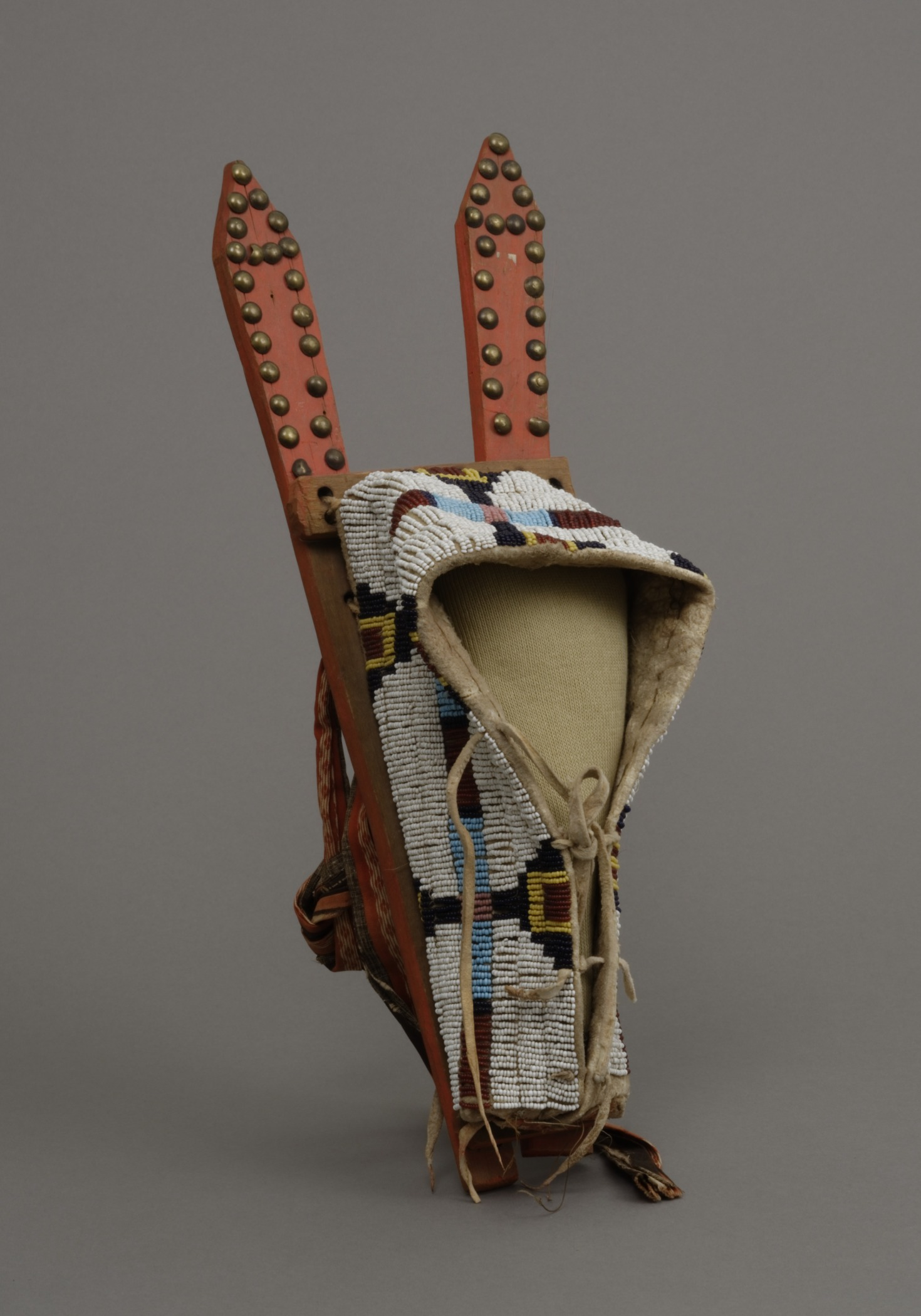 Tsistsistas / Suhtai (Cheyenne), toy cradleboard for a doll, about 1870. Wood, glass beads, hide, brass tacks, cotton cloth, paint, sinew, and thread, 4 3/4 × 16 1/4 × 5 1/2 in. Hood Museum of Art, Dartmouth College: Gift of Mrs. William M. Leeds; 13.13.760.
