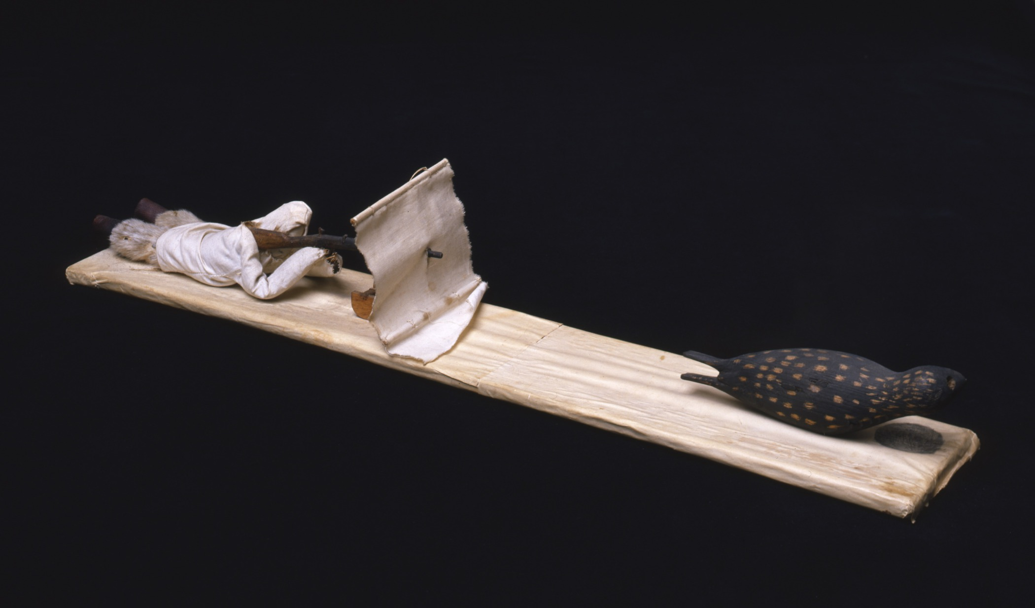 Kalaallit (West Greenlandic Inuit), souvenir model of a man seal hunting in the spring using a blind and a gun stand, early 1930s. Wood, paper, cloth, seal fur, sealskin, commercial thread, and glue, 2 9/16 × 3 3/4 × 22 13/16 in. Hood Museum of Art, Dartmouth College: Gift of George Murphy, Class of 1941; 39.70.7906.