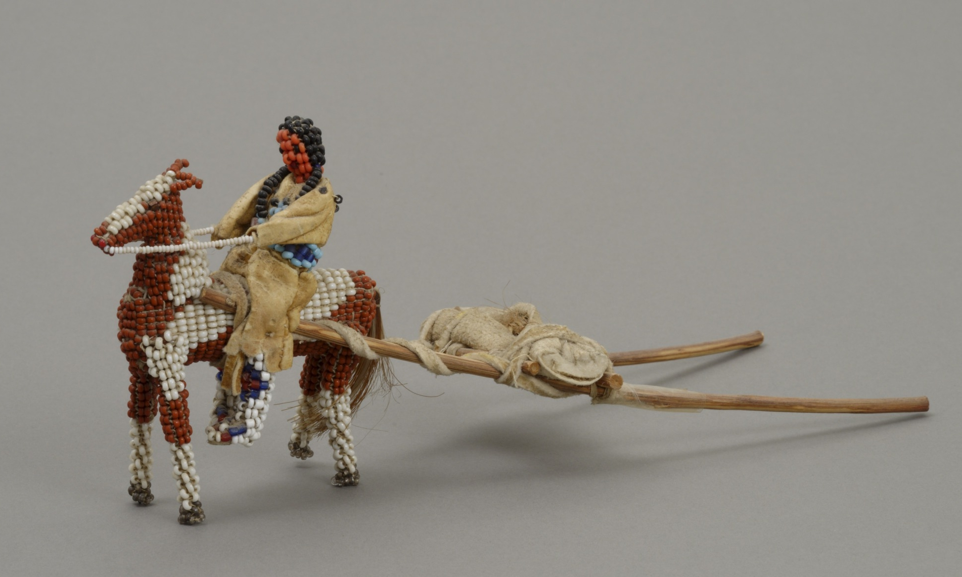 Lena Brown, American (Inunaina), born 1892 , doll representing an Inunaina woman, child, and horse, 1946. Glass trade beads, buckskin, horsehair, wood poles, string, and metal wire, 3 3/16 × 2 7/16 × 7 7/8 in. Hood Museum of Art, Dartmouth College: The Wellington Indian Doll Collection, Gift of Barbara Wellington Wells; 987.35.26800.
