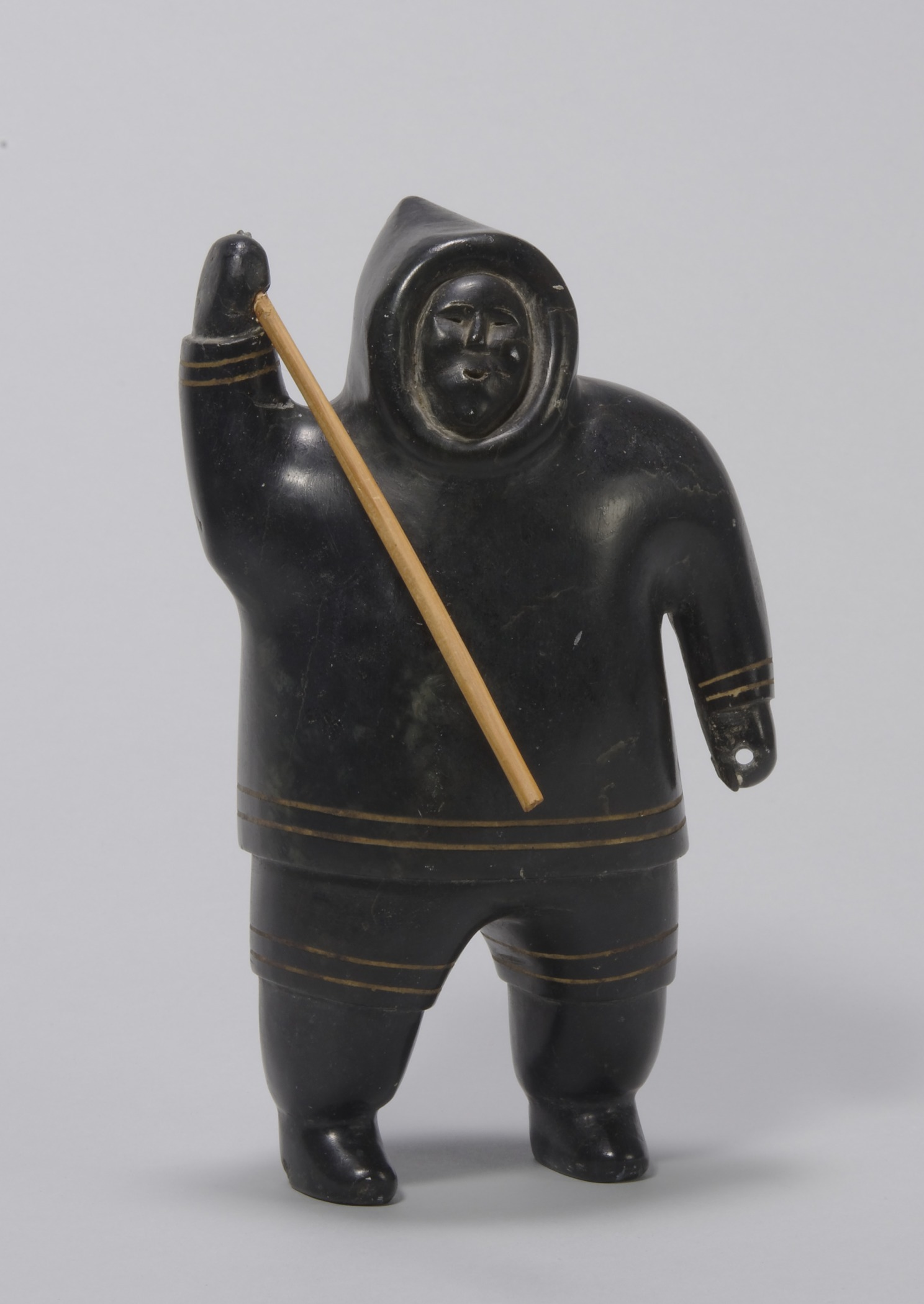 Akeeaktashuk, Canadian (Inuit), 1898–1954, Man in Parka Holding a Spear , about 1952. Serpentine, darkened with shoe polish, with plastic inlay, 8 3/4 × 5 1/8 × 2 15/16 in. Hood Museum of Art, Dartmouth College: Bequest of Evelyn Stefansson Nef; 2014.17.11.