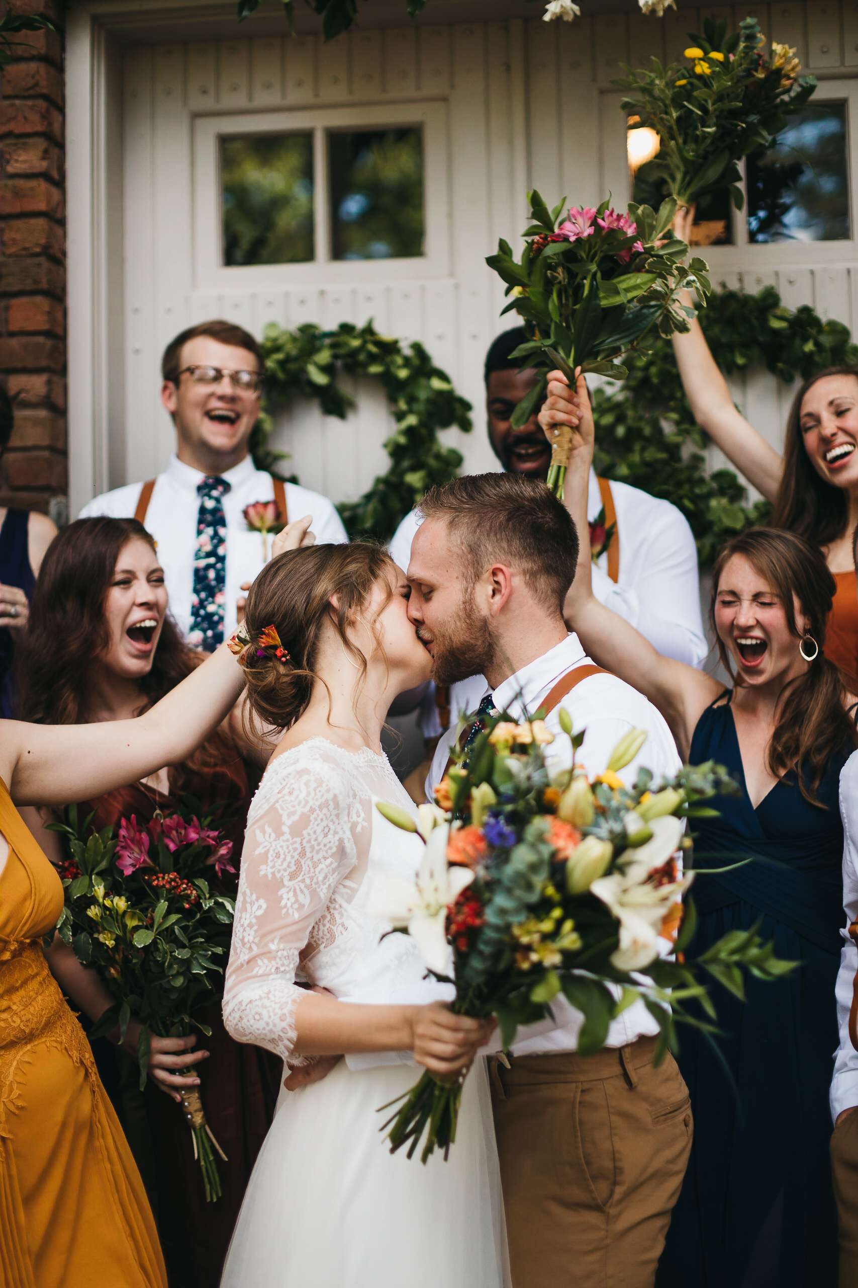 Arkansas Wedding Photographer: Bride and groom kiss while bridal party cheers