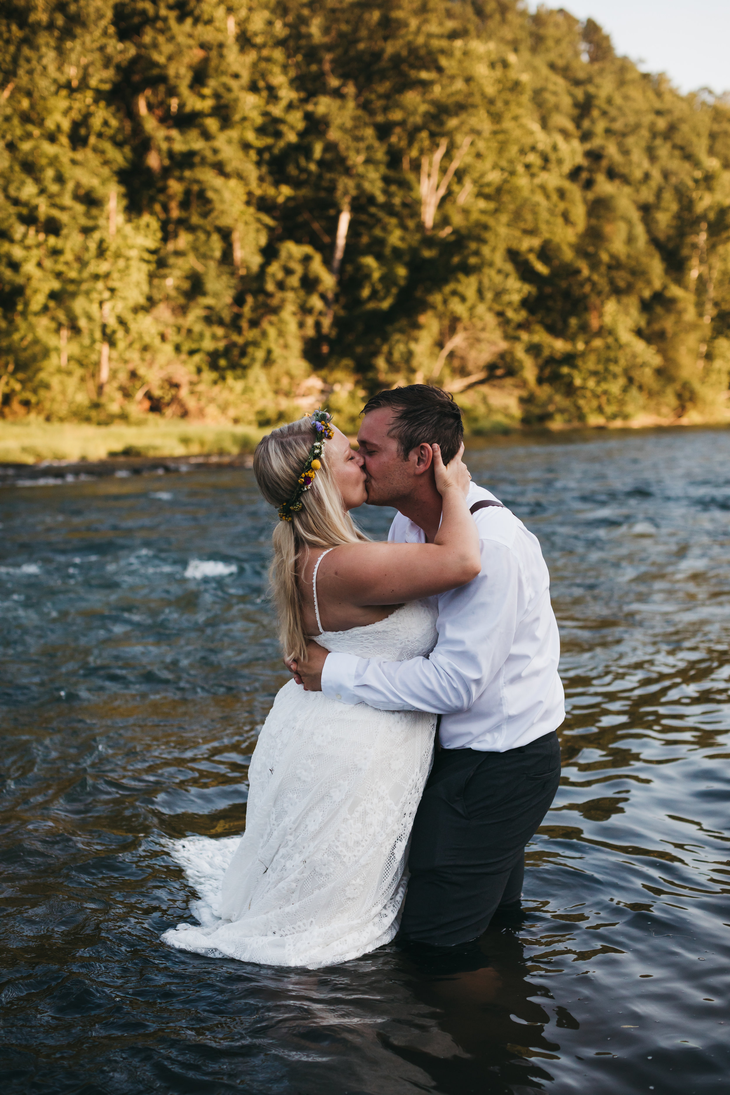 Bride and groom kiss while standing in a river