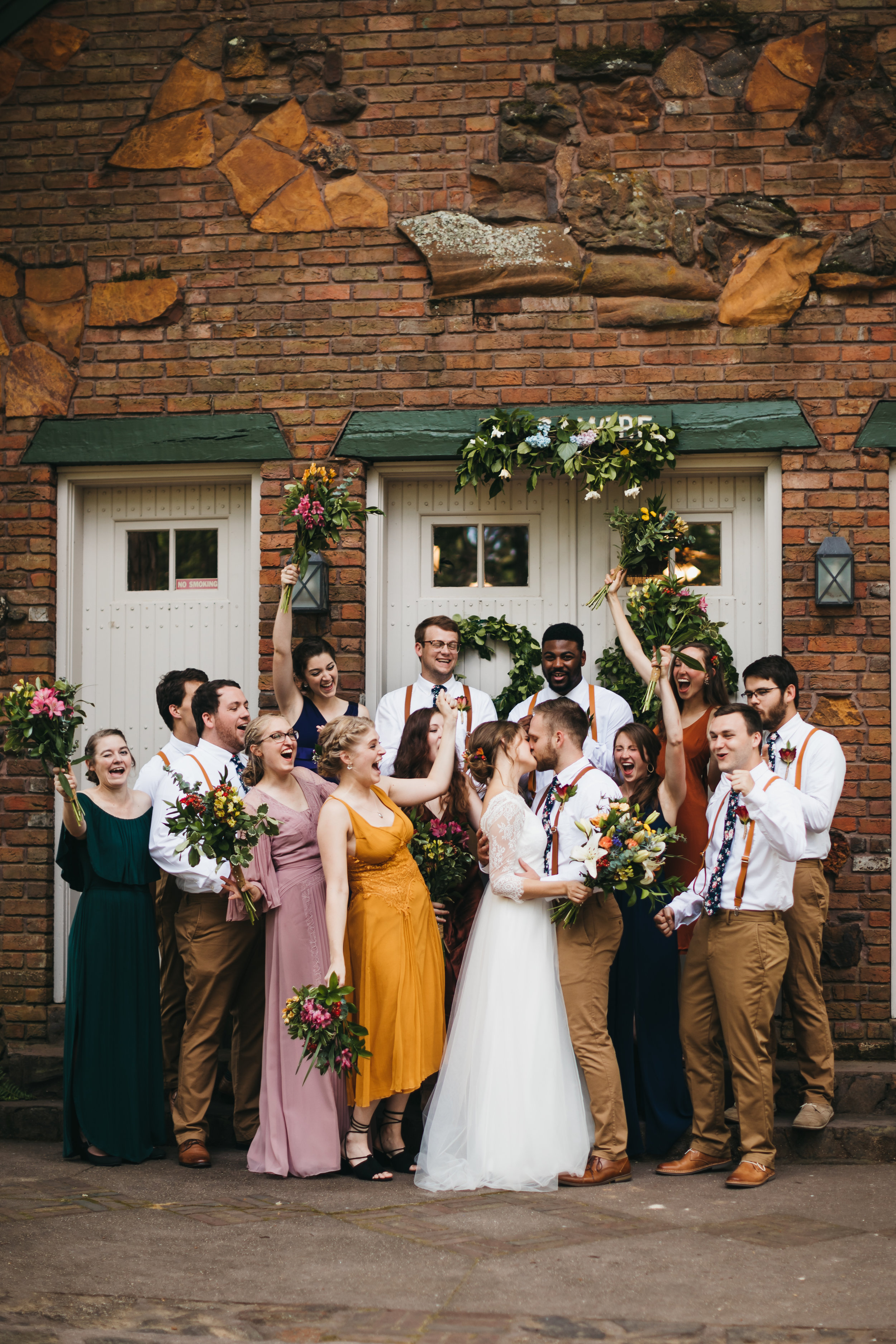 Bridesmaids and groomsmen throw their hands in the air in excitement surrounding the bride and groom as they kiss