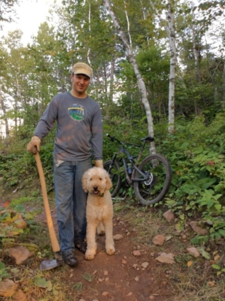 Lester Park Trail steward Mike Reuter stands beside his dog and bike while working on the Hawk Ridge trail.