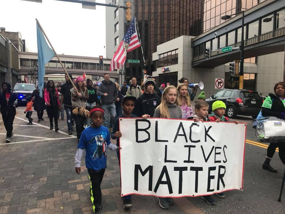 """Community members march down Superior Street during the """"March to Dismantle the Legacy of Racism"""" last Saturday. Photo by Ellie Gerst"""