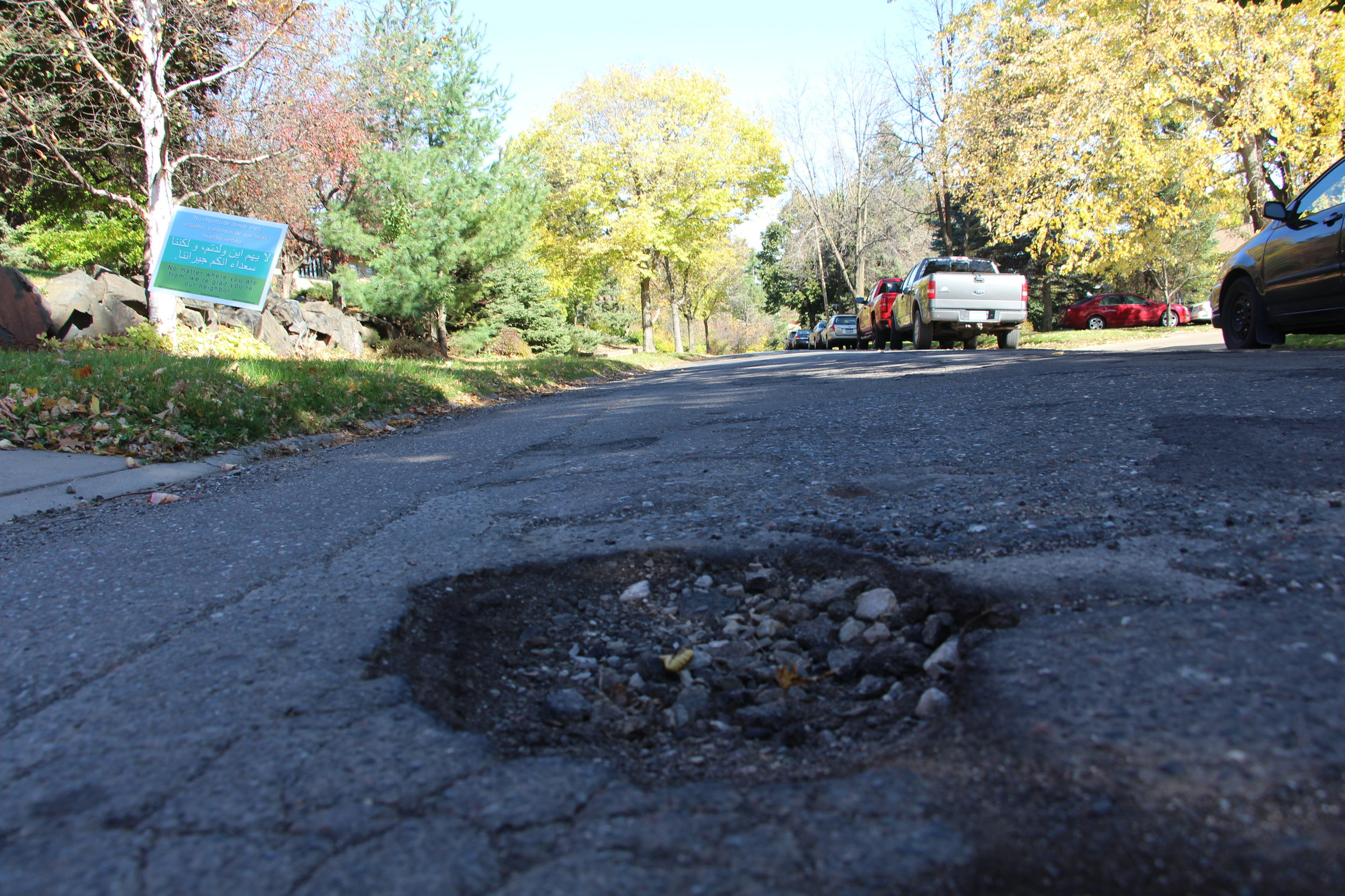 A pothole lurks, waiting to inflict damage on a vehicle's suspension