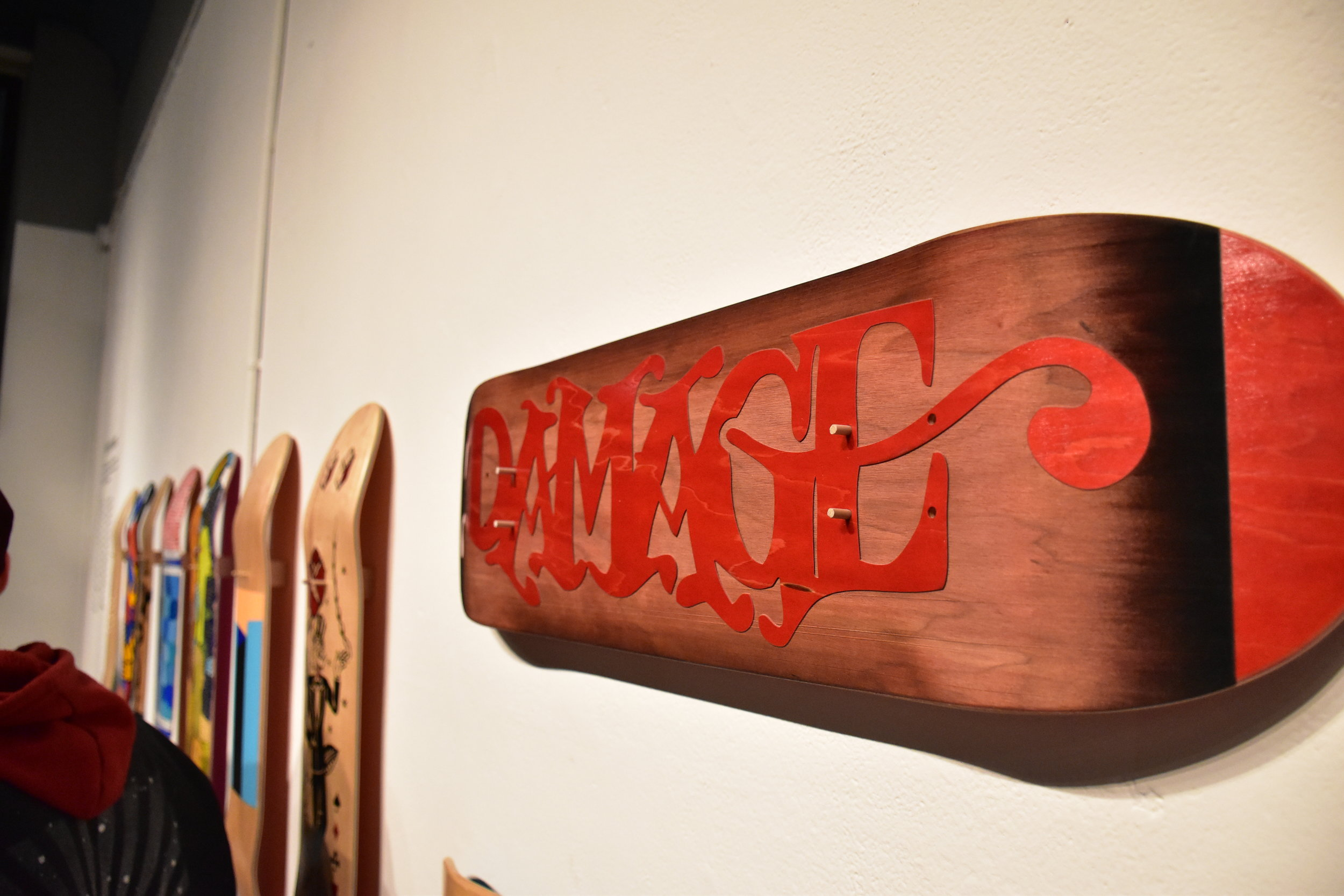 The red on Damage Boardshop's logo stands out against the wood grain of the skateboard -  Photo by Alex Ganeev