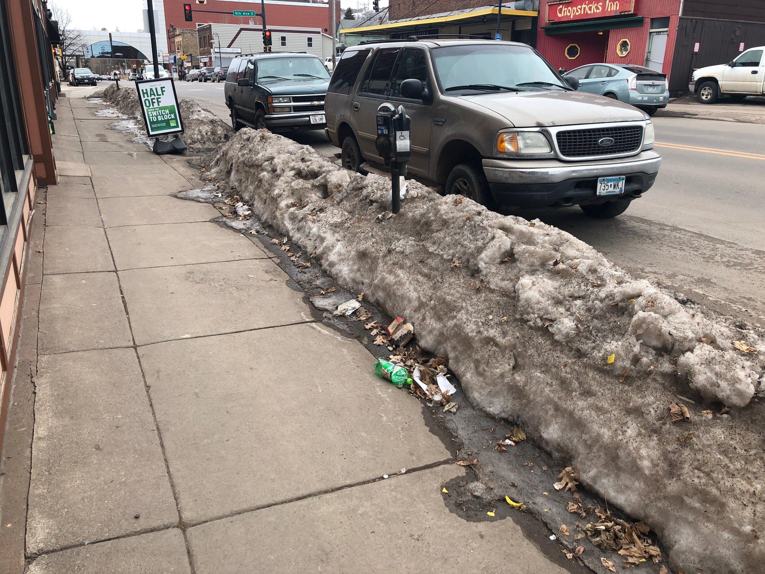 A pile of trash sits on a sidewalk along 4th street