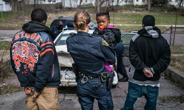 Officer Balasko comforts child as the guardians are escorted away Photo by: Zackary Canepari