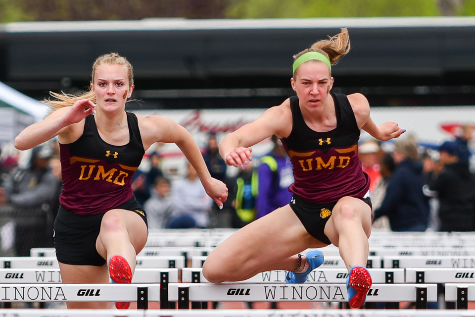 Madison Biebel (left) and Nicole Schneider (right) run hurdles during a meet in Winona. Photo courtesy of UMD Athletics.