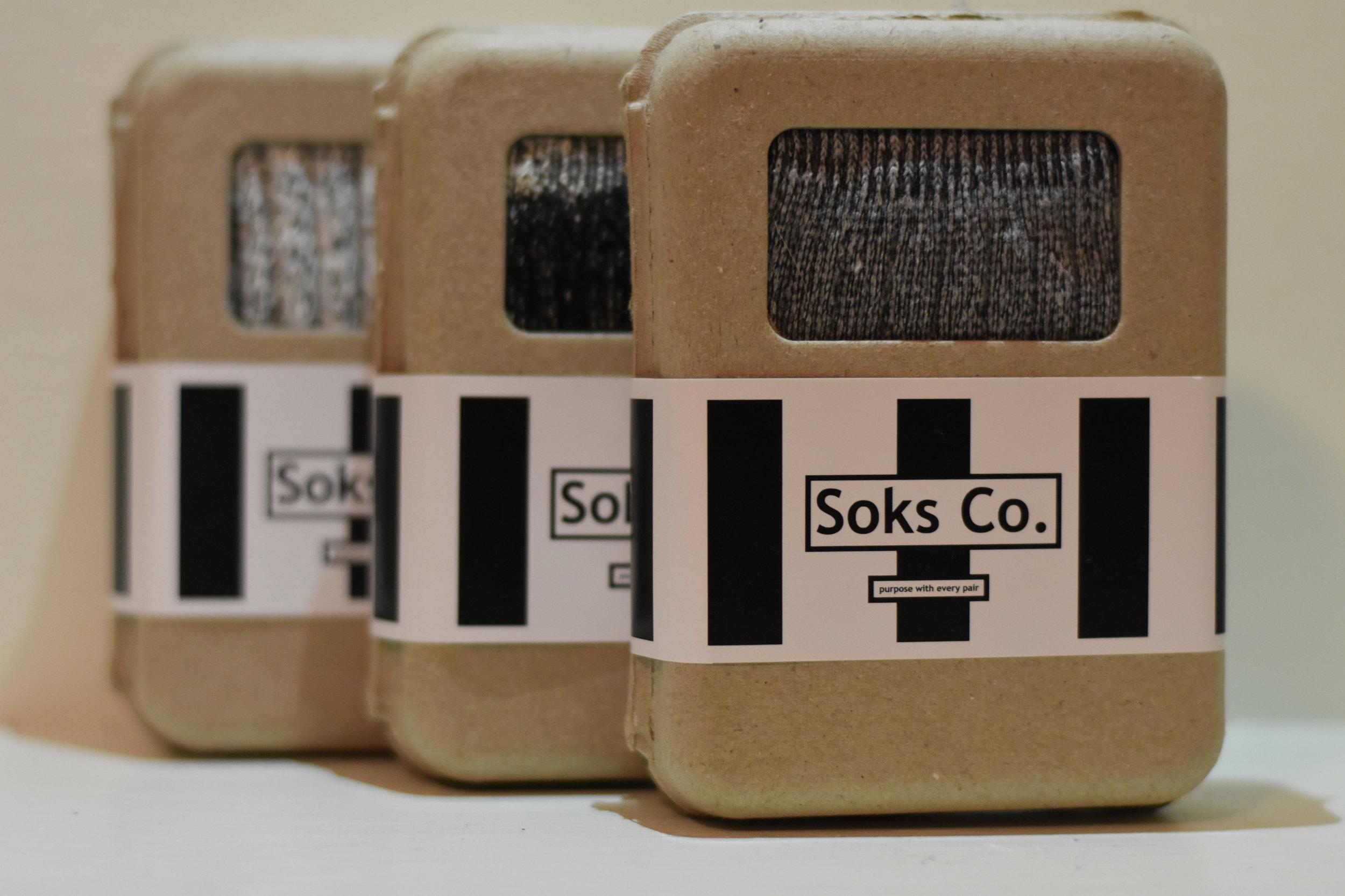 Soks Co. Packages of socks. Grey Original Merino Wool (Closest), Black Original Merino Wool (Middle), and Salt N' Pepper Cable Knit socks (Furthest). Photo courtesy of Austin Nelson.