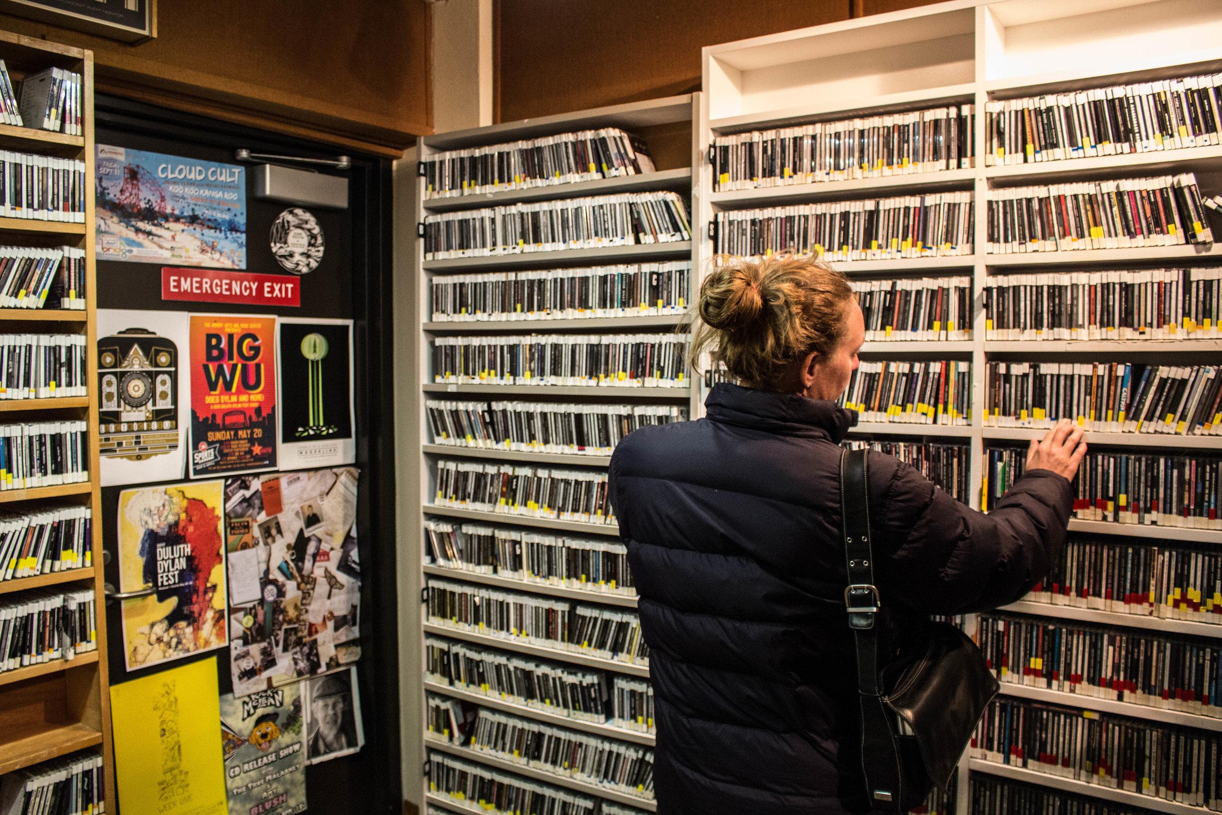 Miriam Hanson looks through CD's at the KUMD Studio. Photo by Justin Flesher
