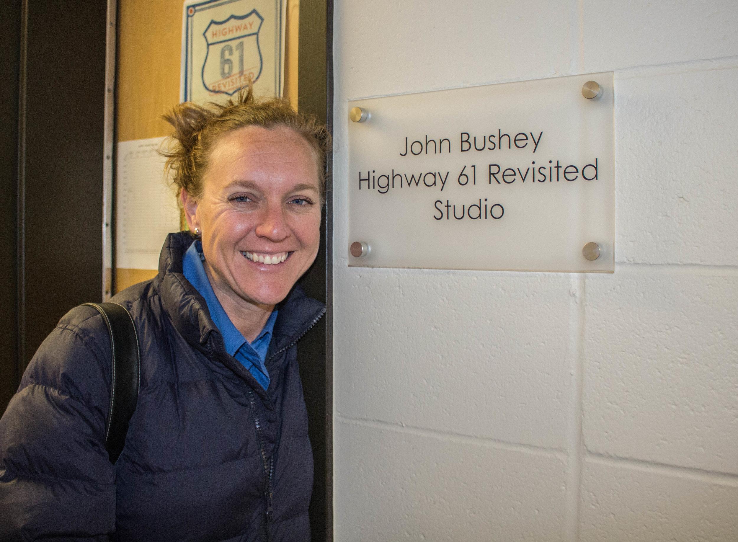 Miriam Hanson poses next to a plaque dedicated to John Bushey in the KUMD studio. Photo by Justin Flesher
