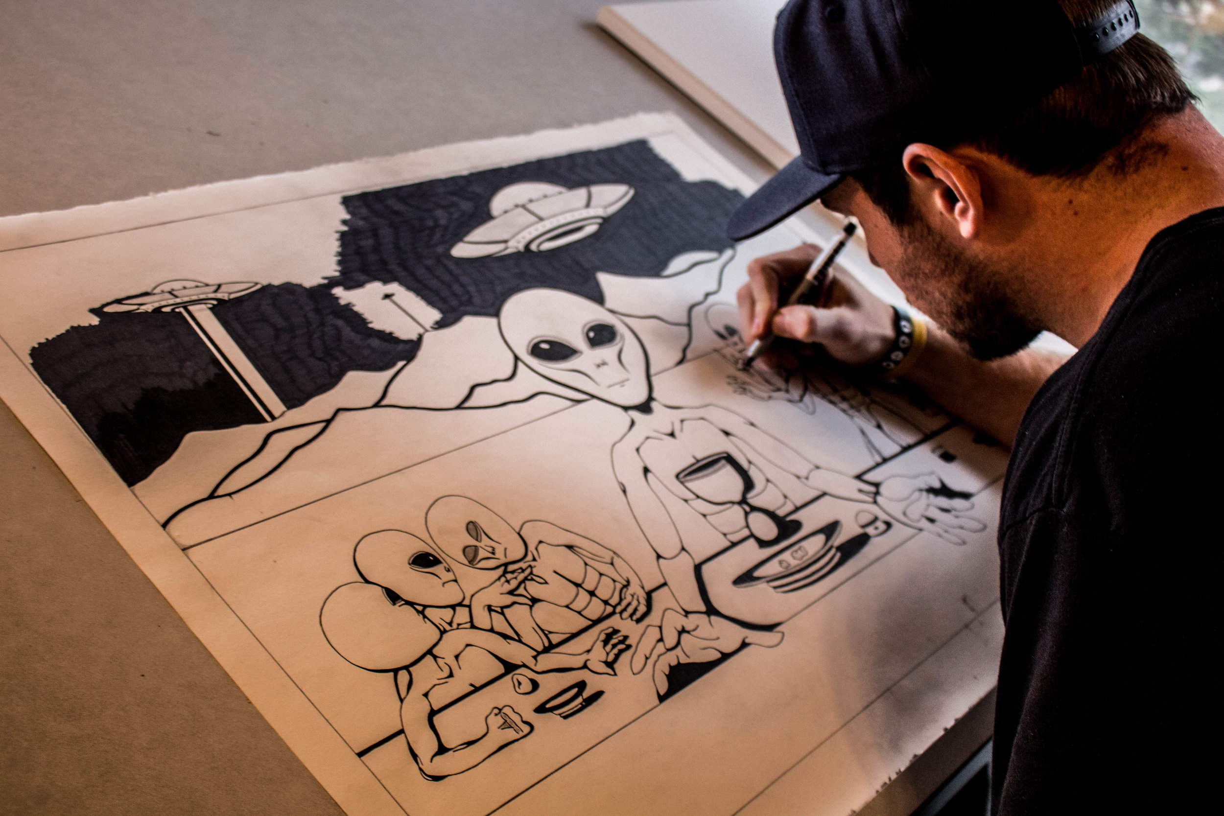"""Dwyer sits in his room working on a drawing he calls """"The First Supper"""". Photo by Justin Flesher"""