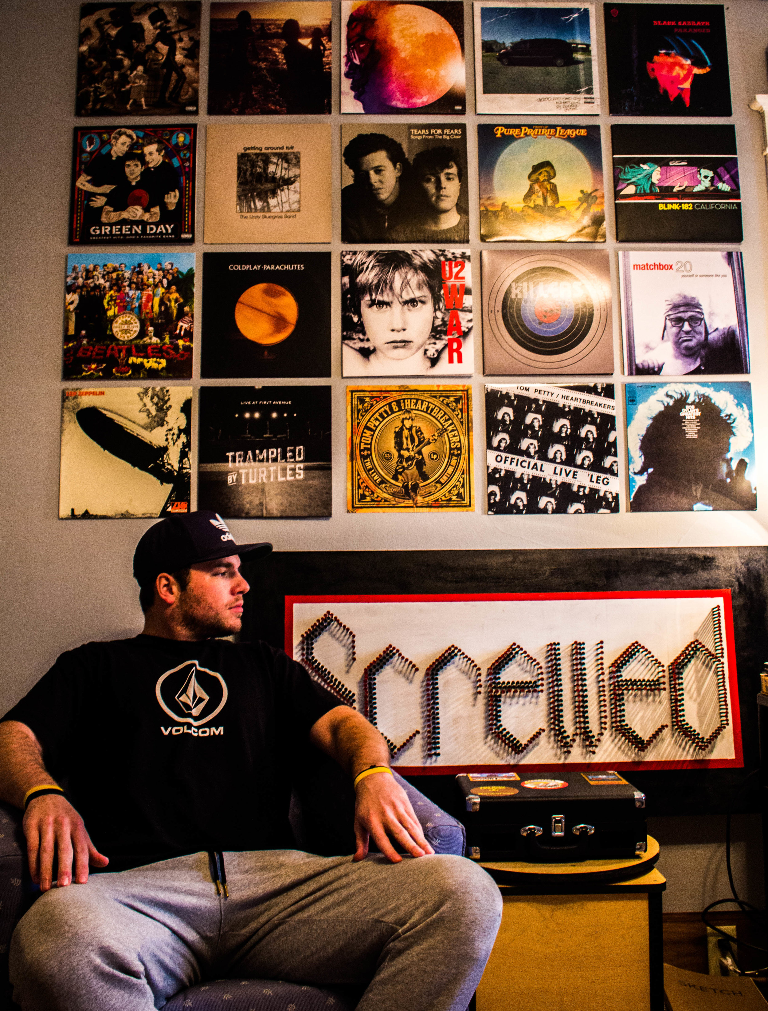 """Mark Dwyer sits in his room in front of his prized vinyl collection and a typography project he calls appropriately named """"Screwed"""". Photo by Justin Flesher"""
