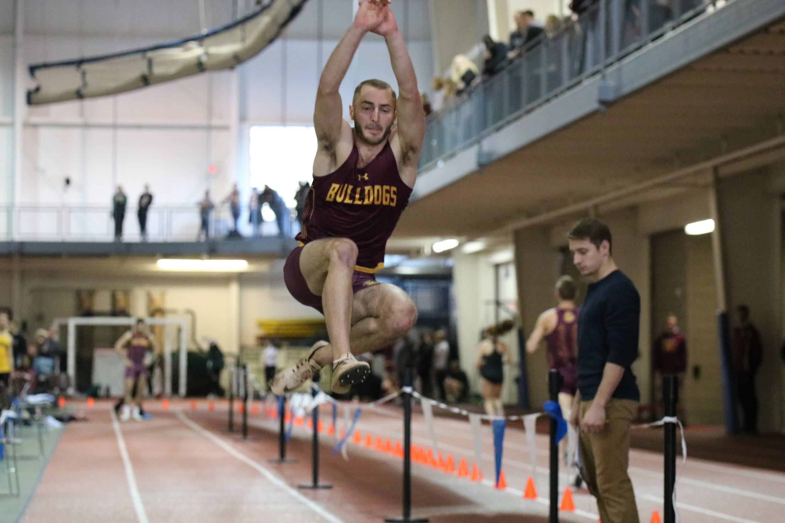 Ryan Tolkinen going airborne in the long jump. Photo by Drew Smith