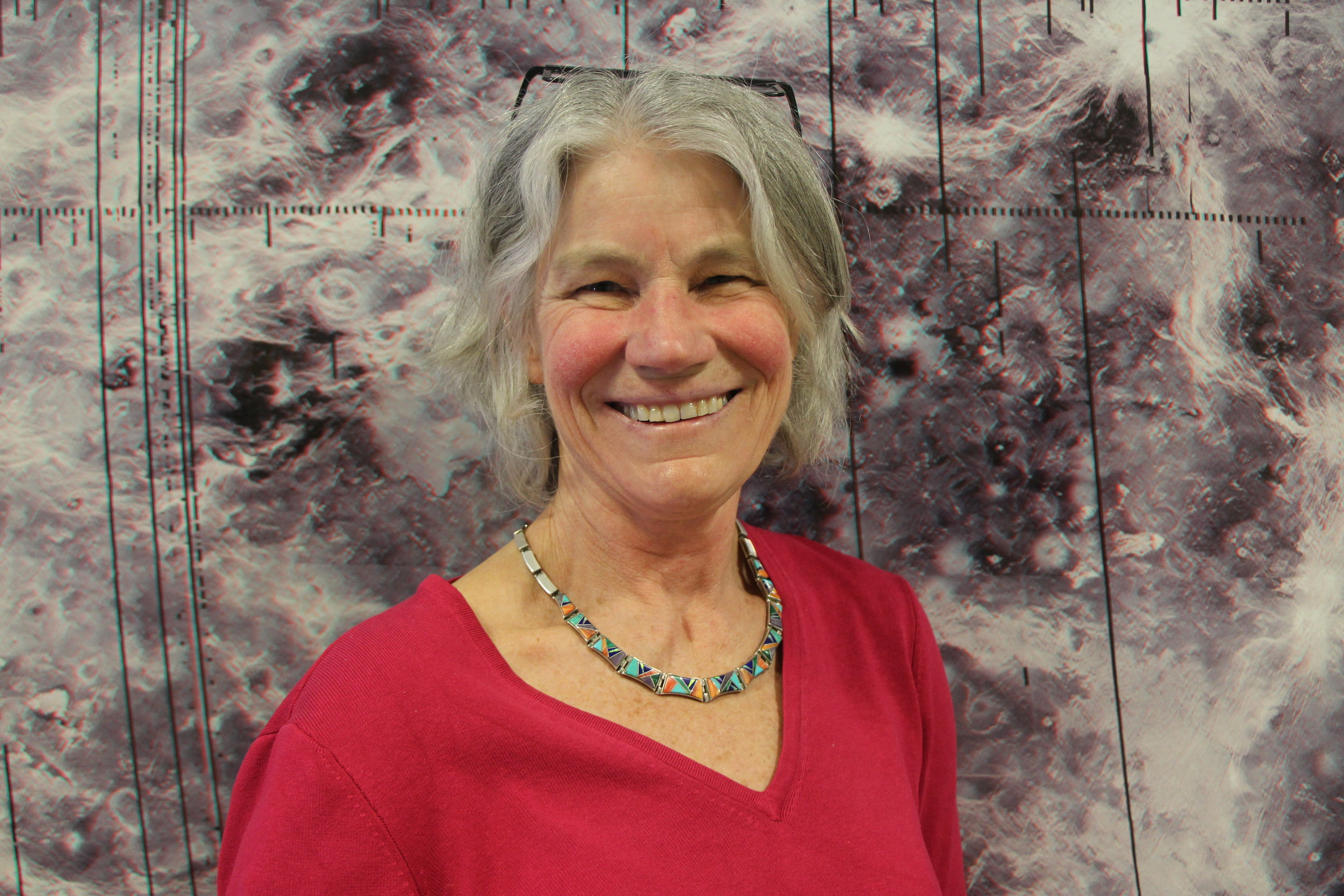 Professor Vicki Hansen posing in front of the Venus Wall Mural. Photo by Suenary Philavanh