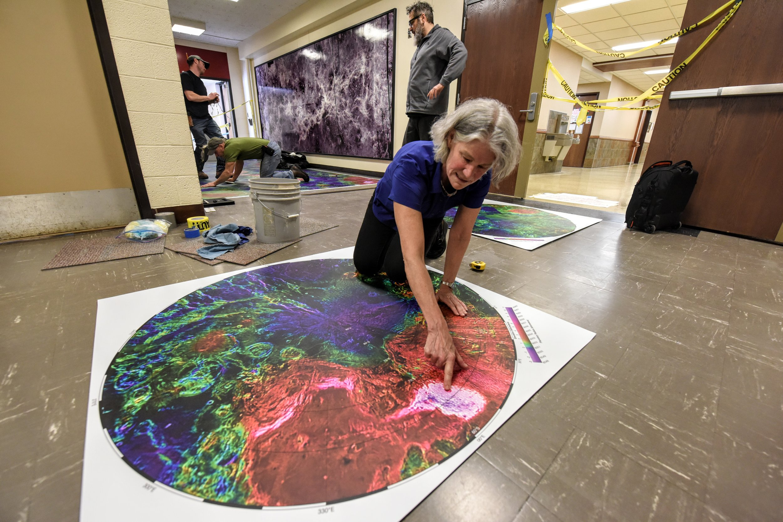 Hansen kneeling over a Venus map during installation. Photo by Valerie Coit