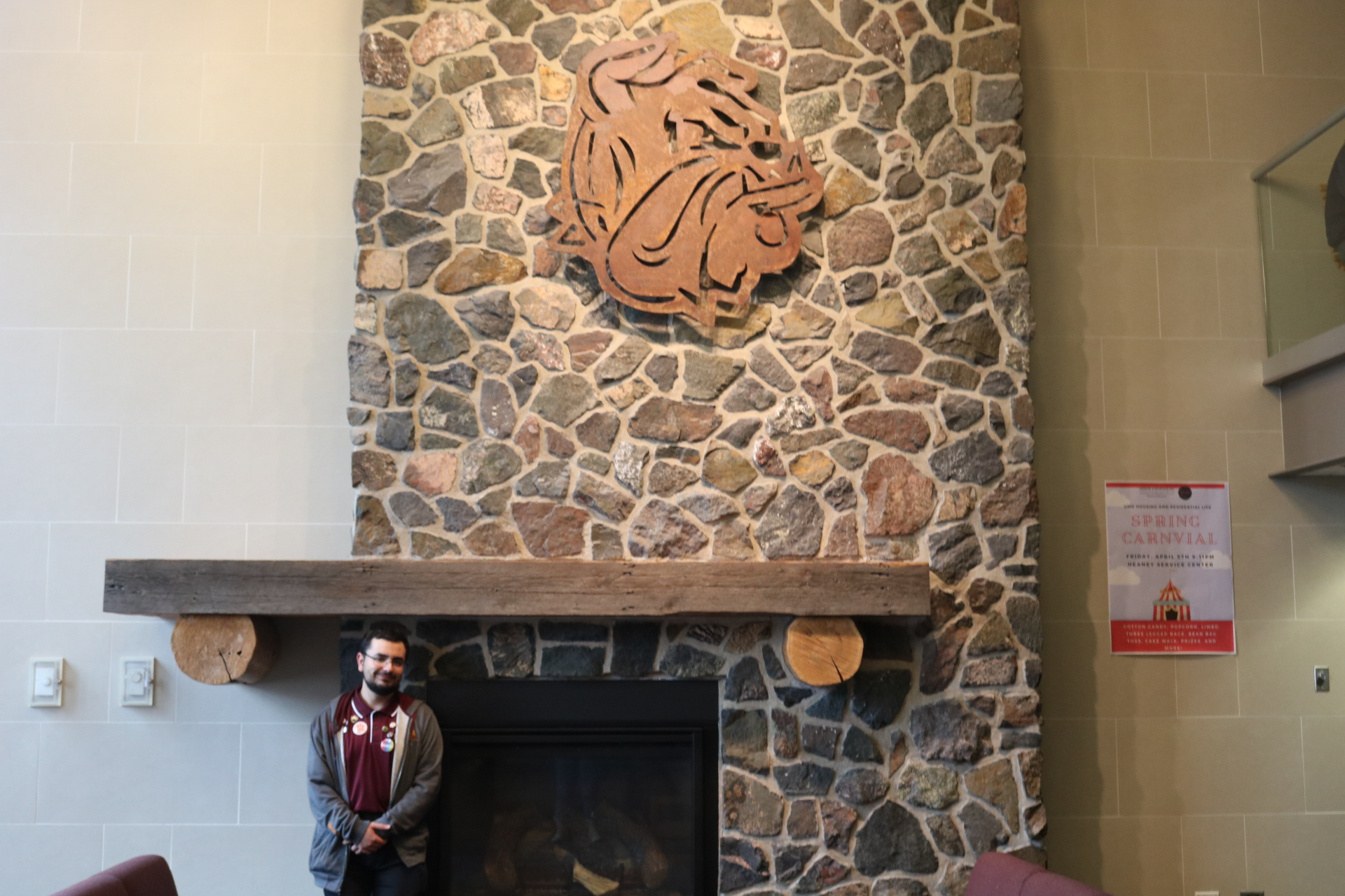 Farahid poses next to the fireplace in Ianni, an homage to Accepting You - The Hearth Guild's name. Photo by Madison Hunter