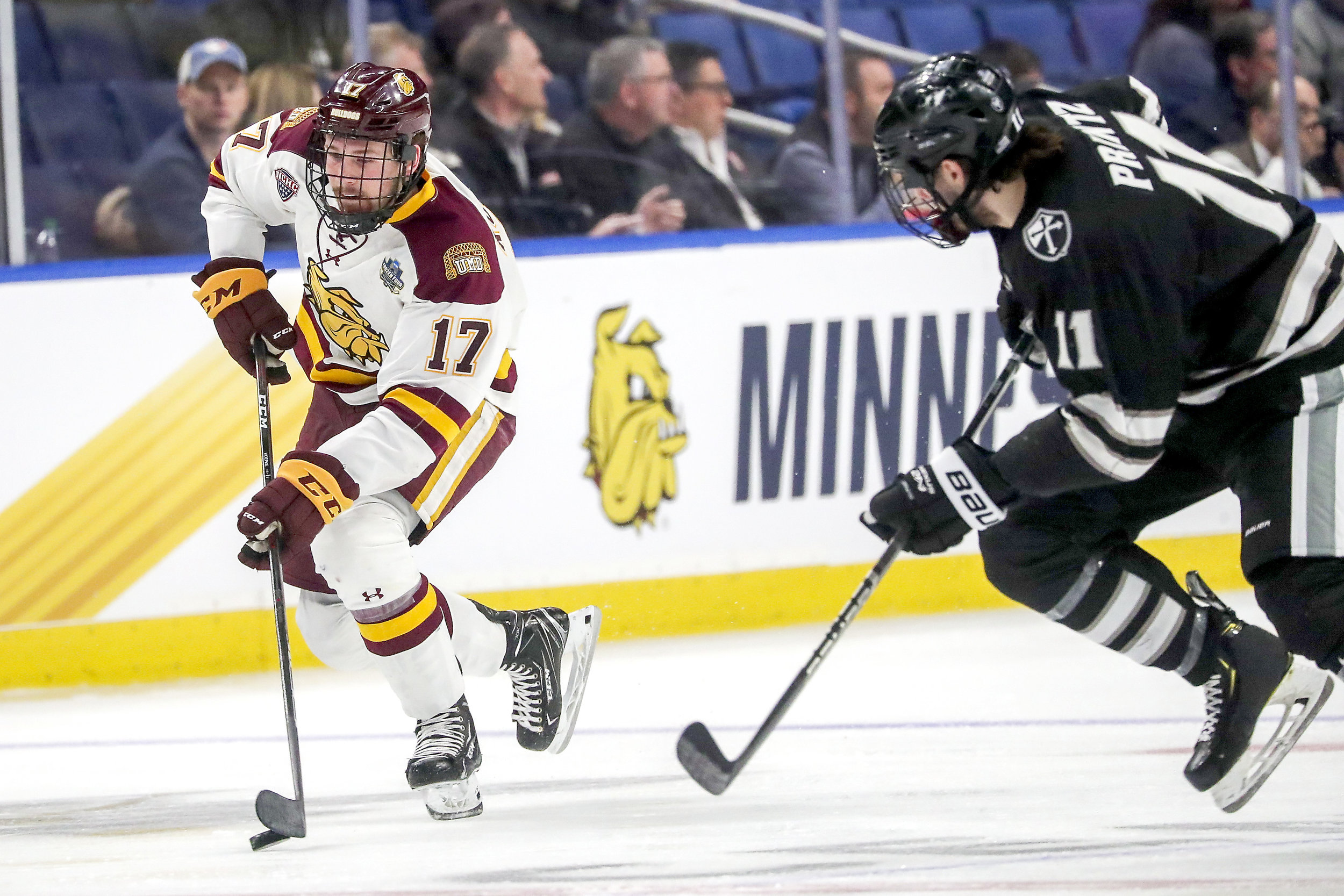 Cole Koepke (17) keeps the puck away from Friars forward Greg Printz (11) during the 2019 Frozen Four. Photo by: Clint Austin