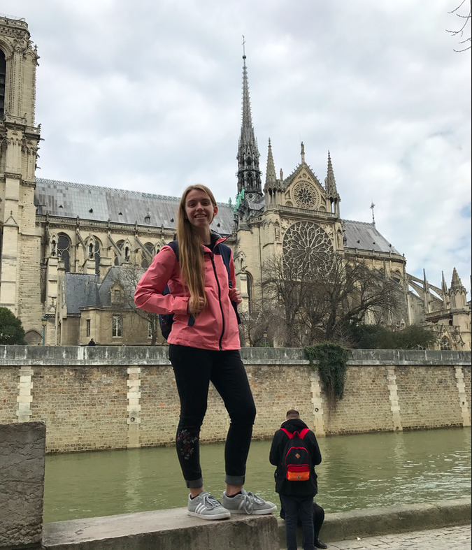 Photo of me with Notre Dame and the large spire in the back