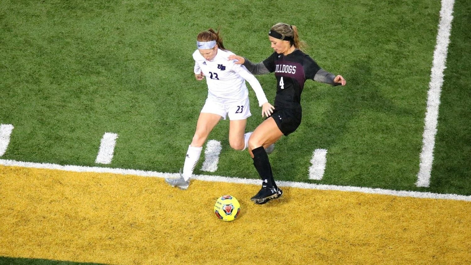UMD sophomore forward Haley Ford battles Bridgeport midfielder Abigail Befford for the ball in Thursday night's match. The Bulldogs would end up winning 3-2. (Photo courtesy of Drew Smith/UMD Athletics)