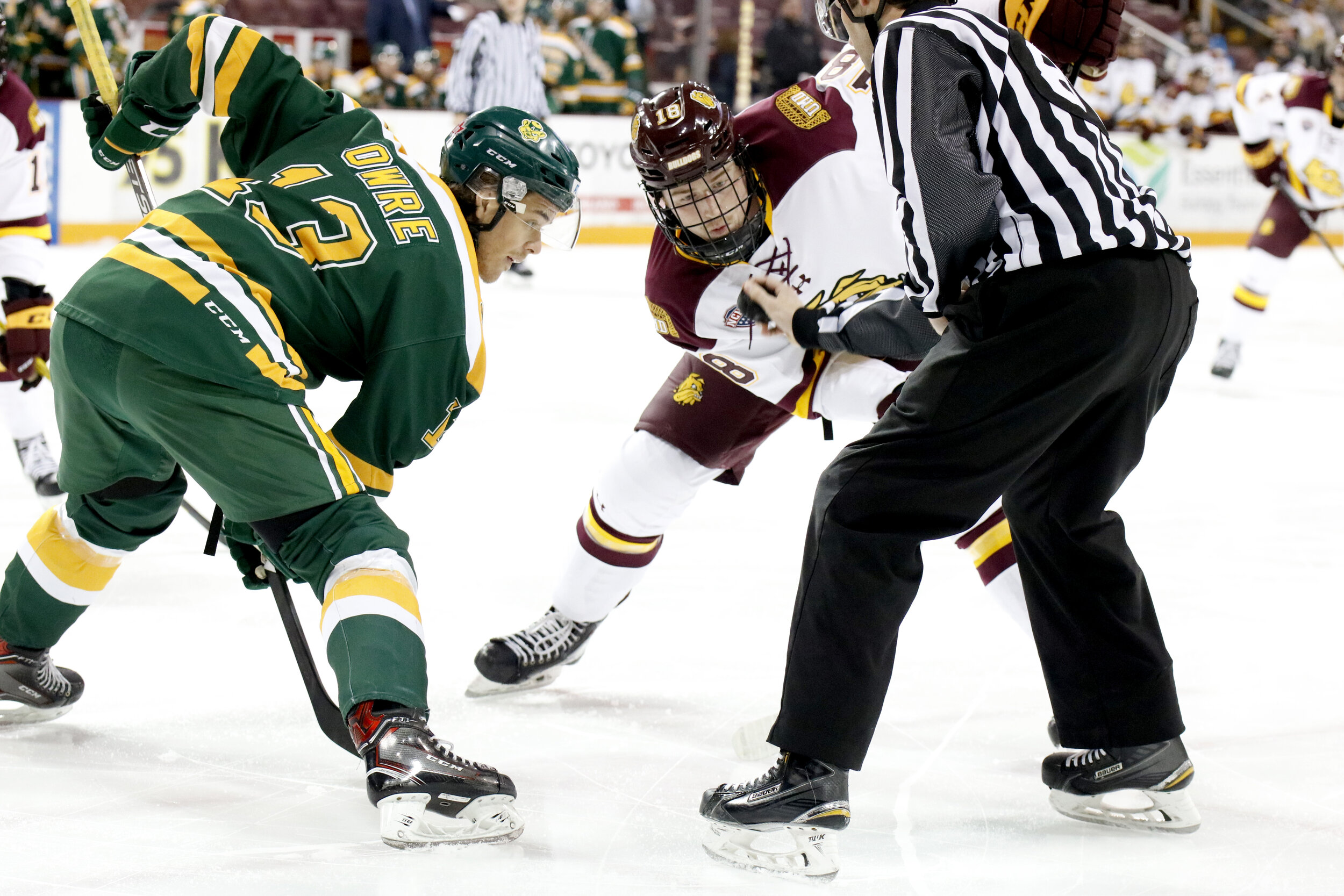 Sophomore center Jesse Jacques (18) takes a face off against Steven Owre (13) of Alberta during Saturday night's exhibition contest. The Bulldogs would go on to lose 5-3. (Photo courtesy of Drew Smith/ UMD Athletics )