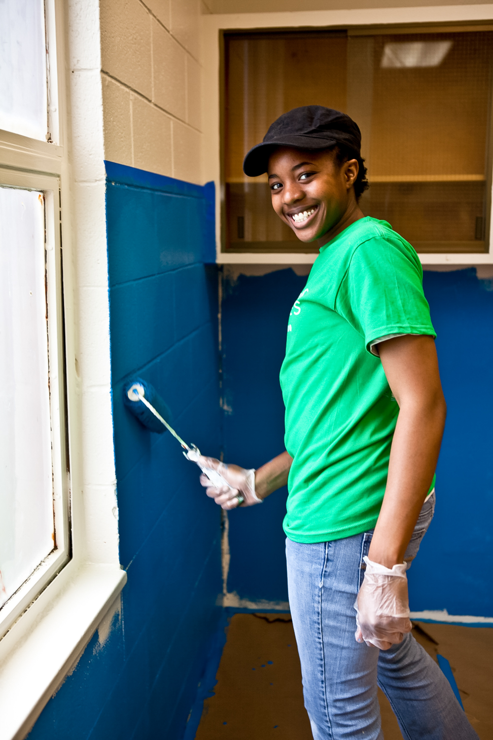 Woman smiling and painting wall at non-profit volunteer event