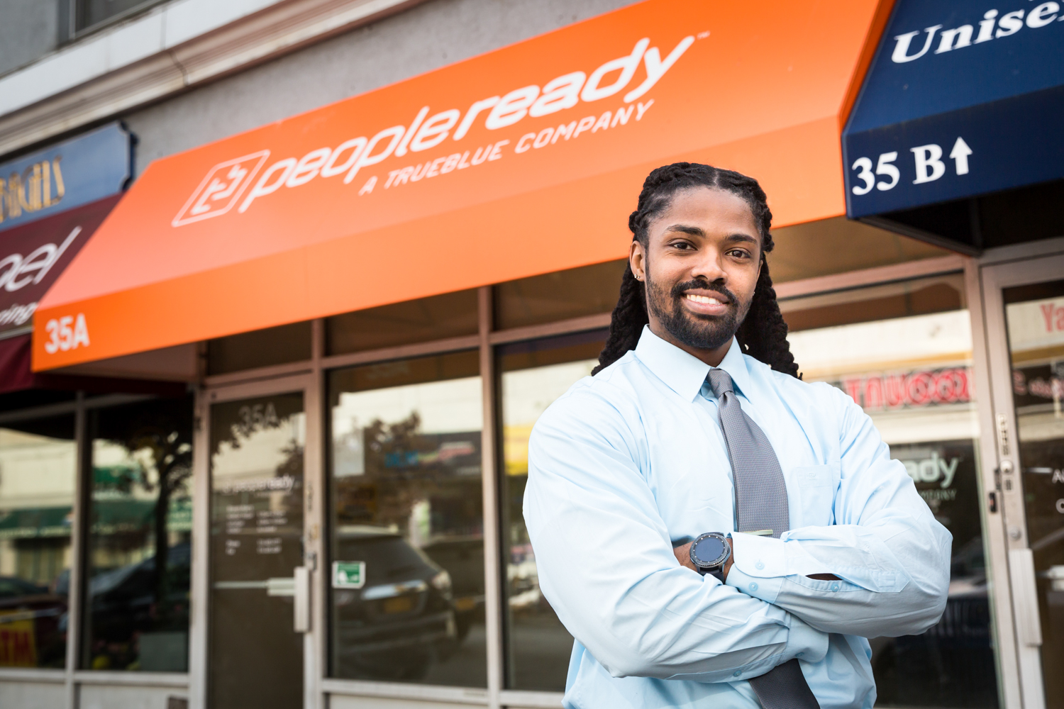Man with arms crossed standing in front of building with orange awning